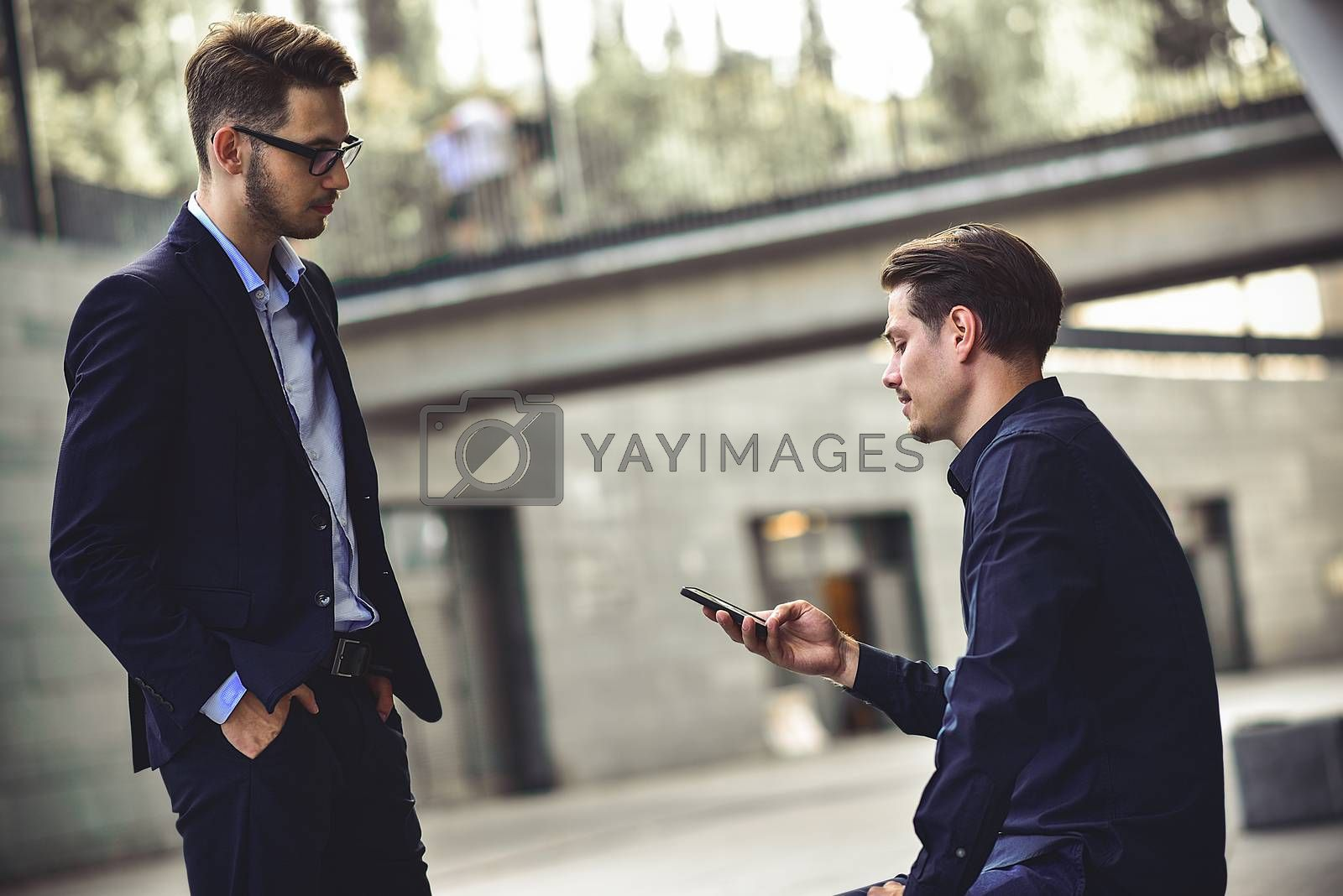 Upset young caucasian man reading a message on his mobile phone.