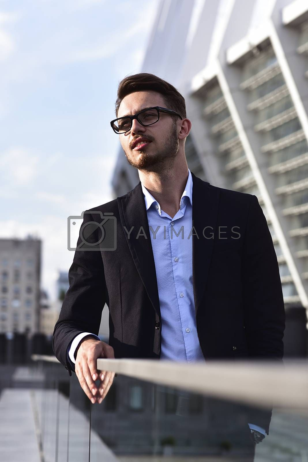 Modern businessman. Confident young man in full suit standing outdoors with cityscape in the background