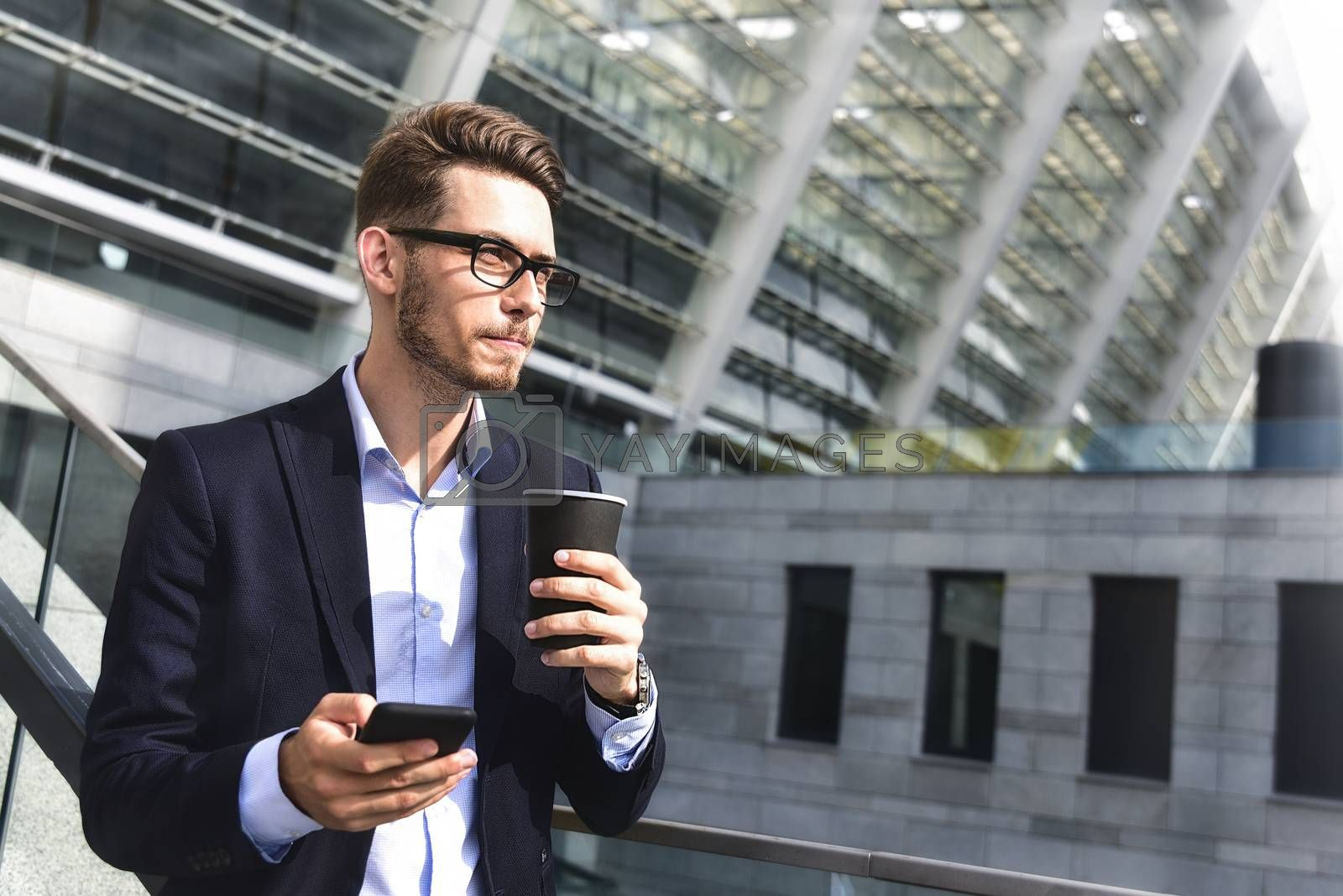 Handsome successful businessman in elegant suit outdoors stand at street in the city with coffee.