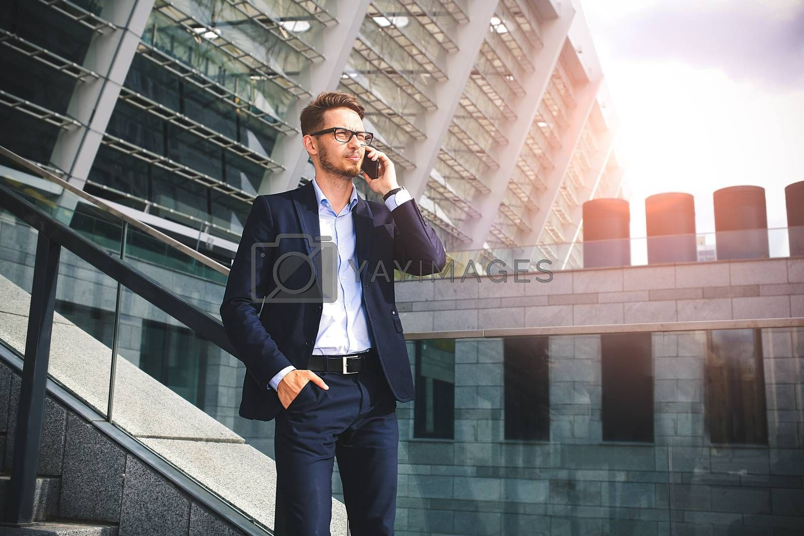 Handsome successful businessman in elegant suit outdoors walking on street in the city.