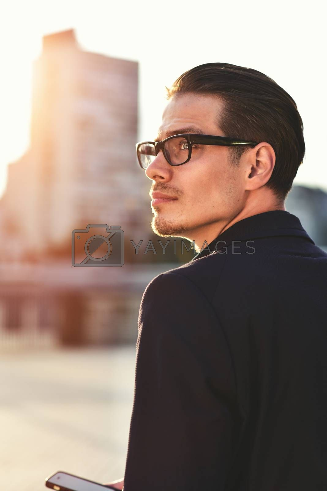 Serious Caucasian businessman dressed at classic wear standing at the street