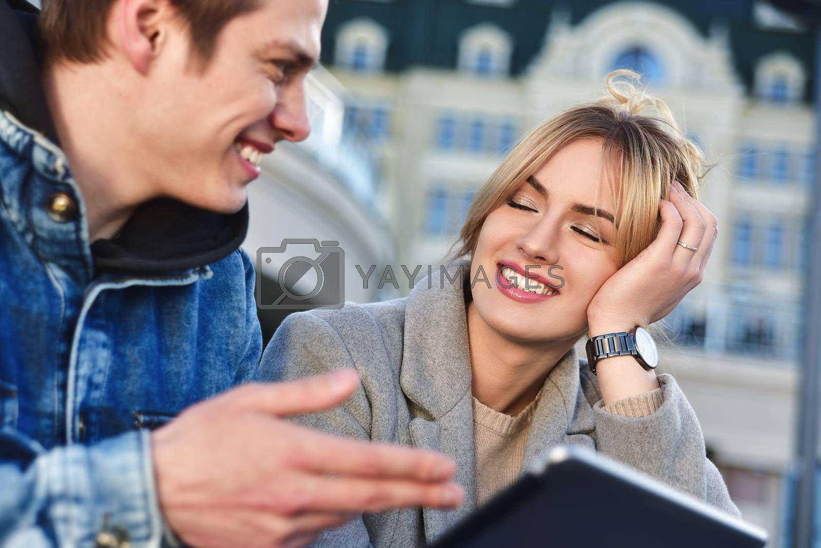 Attractive young couple sitting on floor in urban street reading information on a tablet with a smile