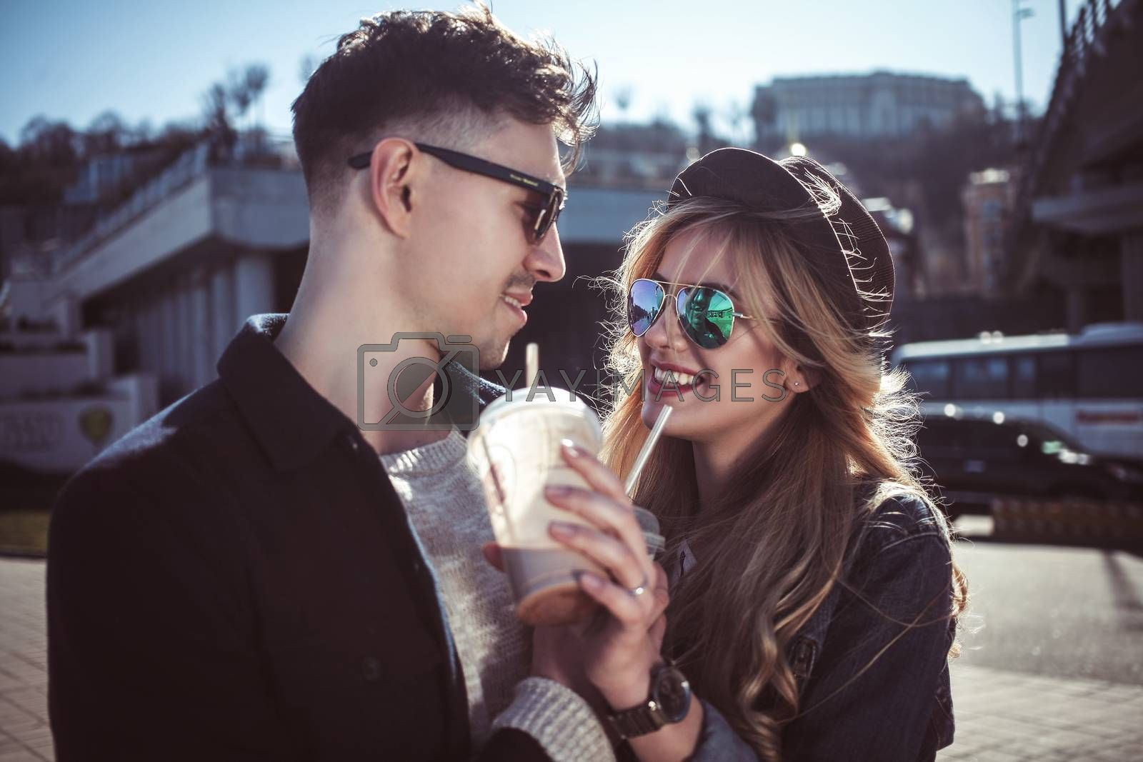 Cute couple having fun walking at the street and drink cocktails , good day