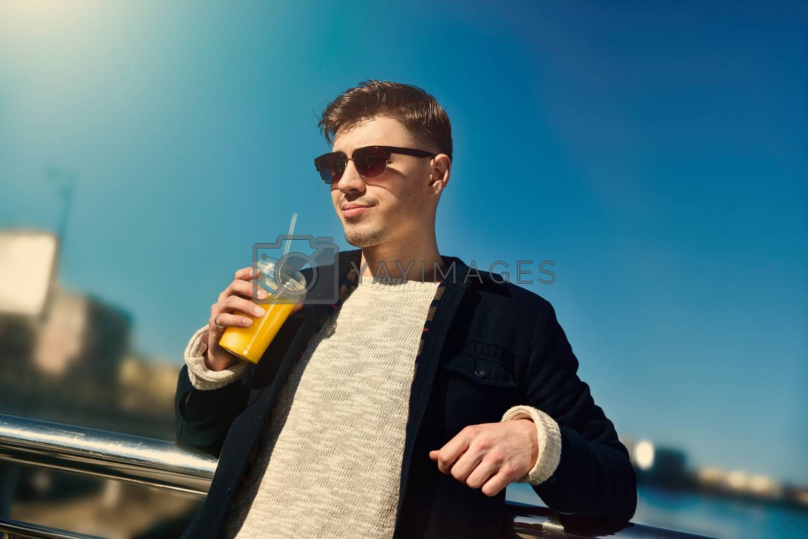 Cute guy with sunglasses holding juice at embankment