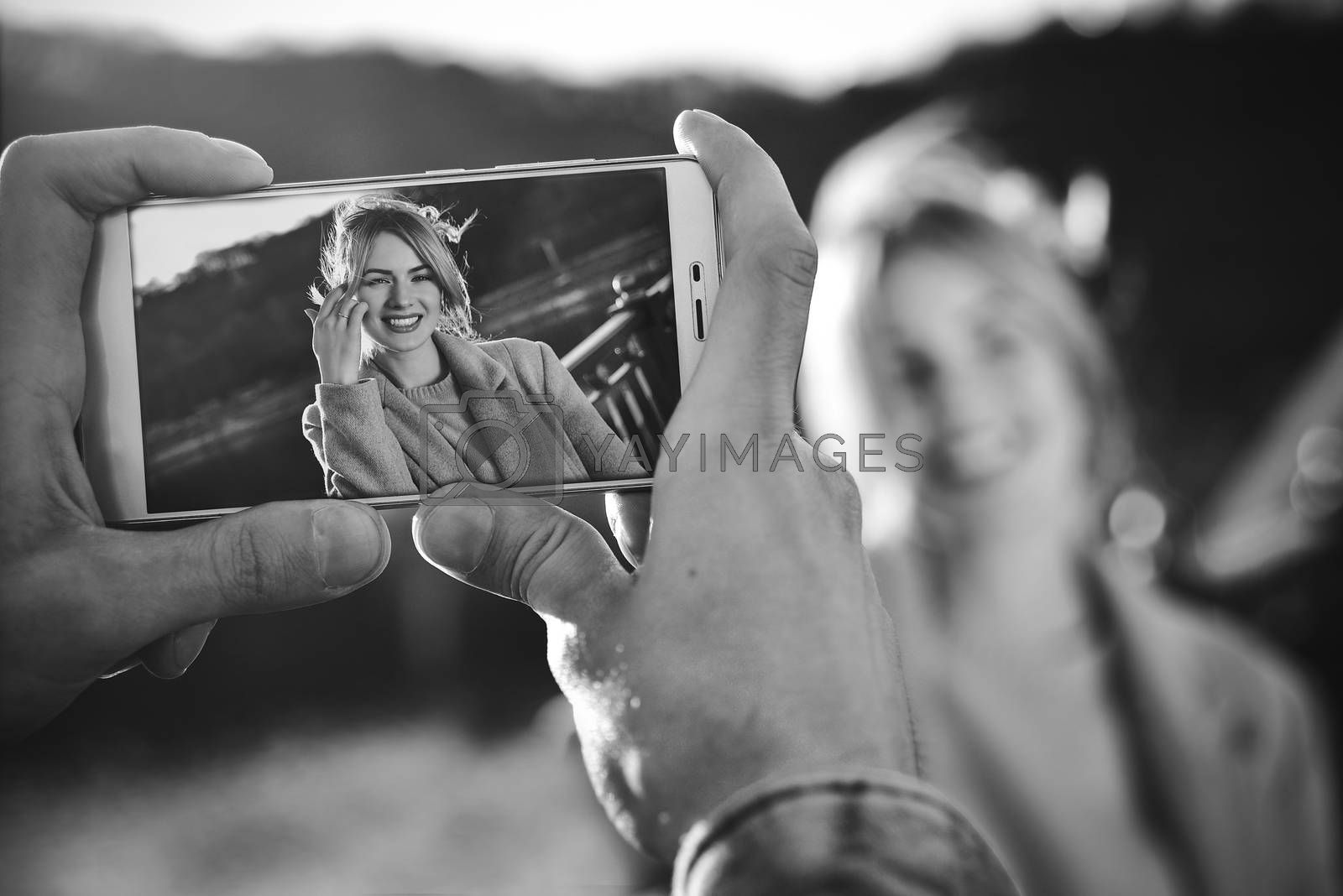 A man make a portrait on the phone of happy smiling woman standing on the bridge on sunny spring or autumn day outdoor