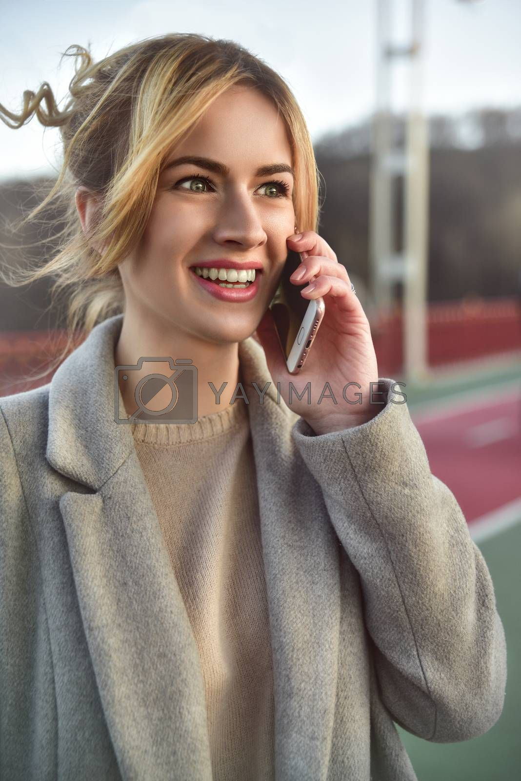 Cute smiling young woman talking on phone standing on the bride. Close up portrait