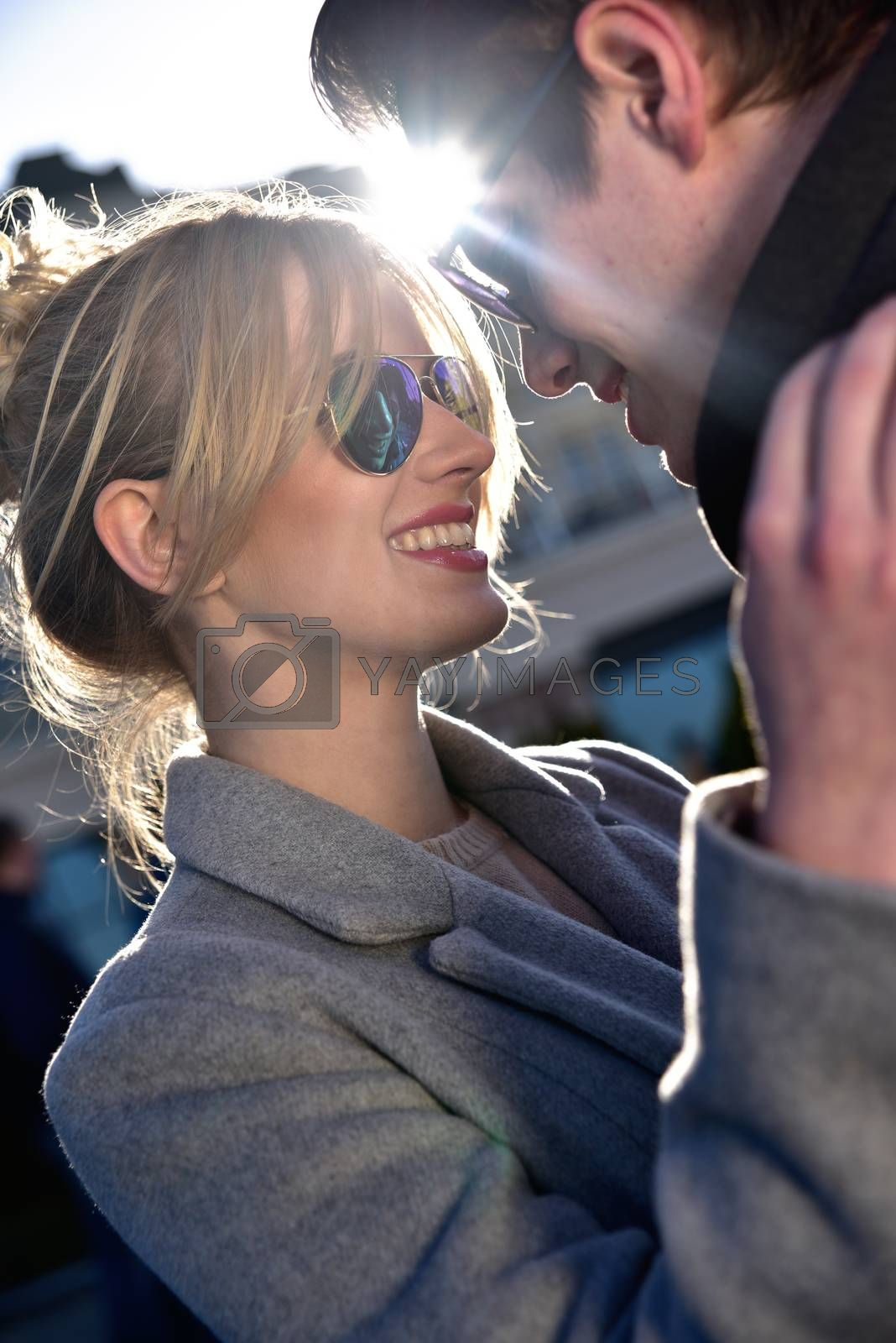 Happy playful couple in sunglasses in love dating joking and laughing in the street