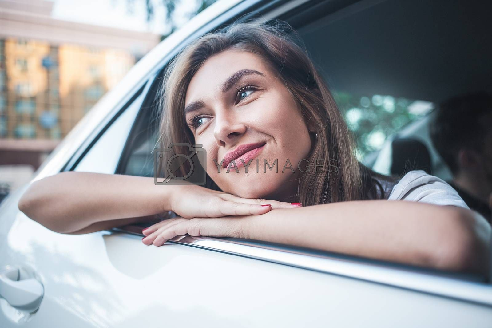 Portrait of cute smiling girl sit in the car and look at the street