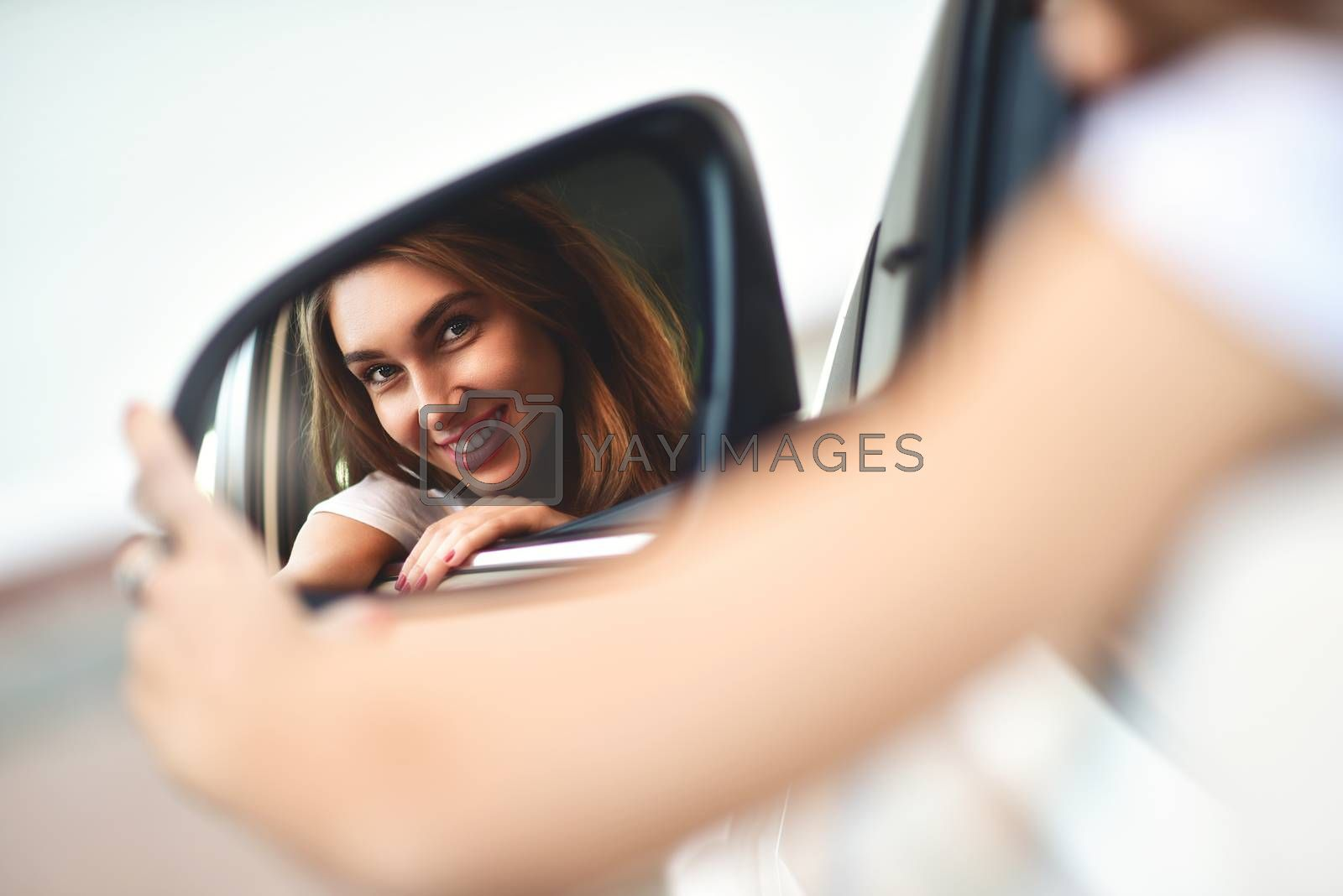 Portrait of cute smiling girl sit in the .car and look at the car mirror