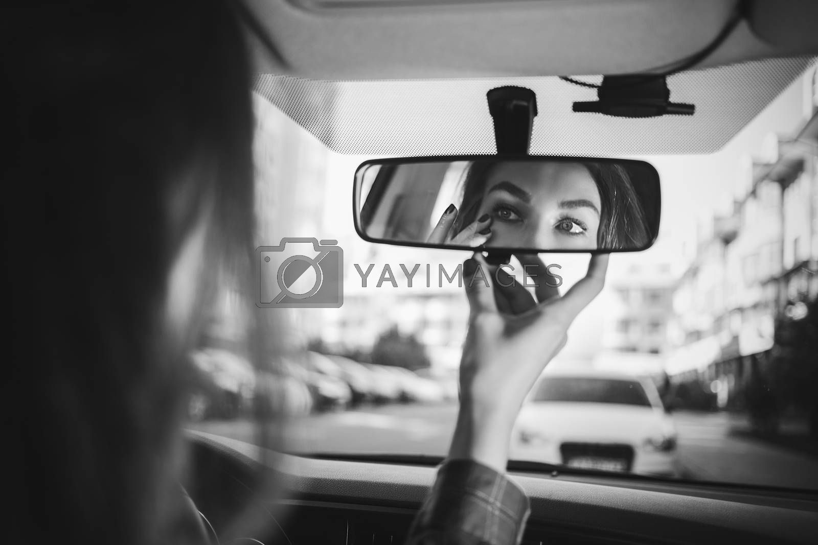 Young woman looking in rear view mirror and putting make up in car. modern busy life.beautiful girl sitting in drivers seat of car doing make up, applying lipstick.