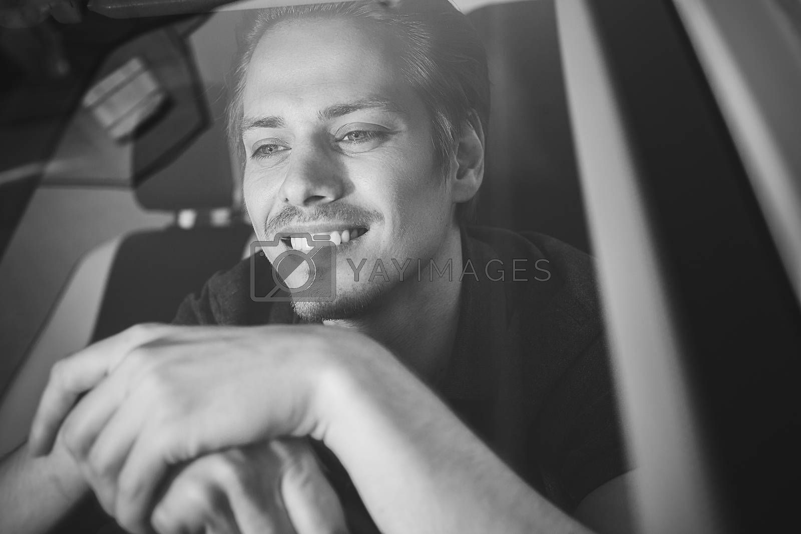 Enjoy the drive. Image of young handsome guy sitting in car.