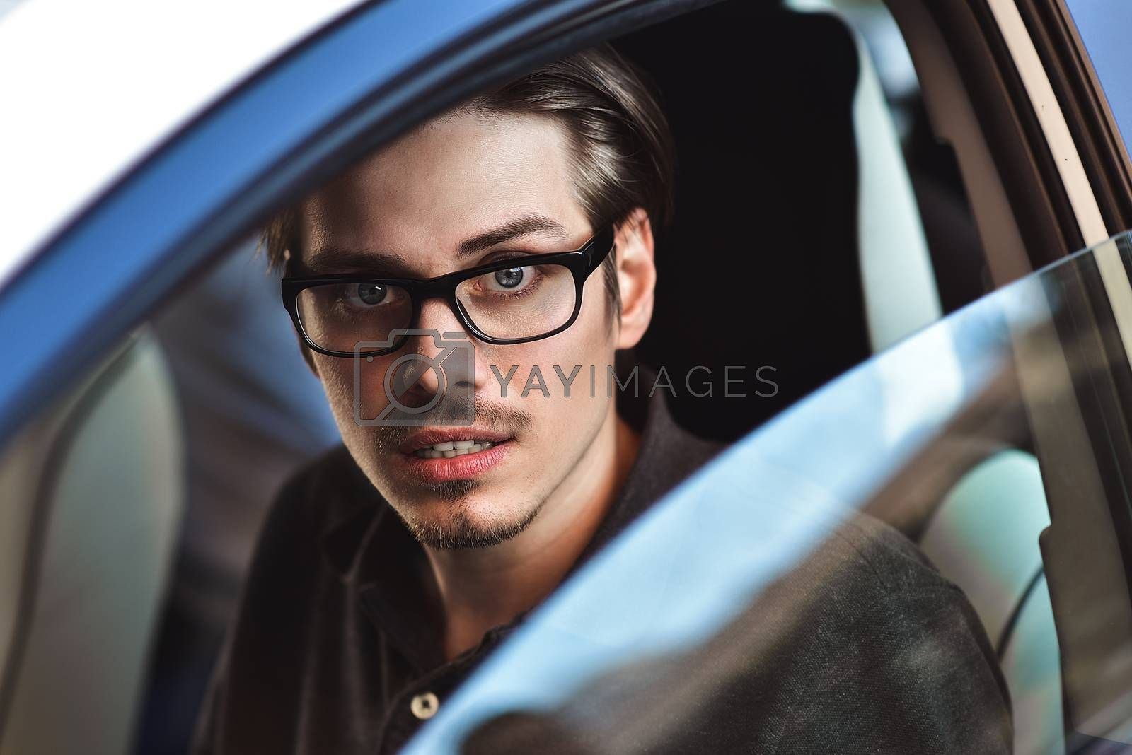 Close up side portrait of caucasian man driving car. by Nickstock