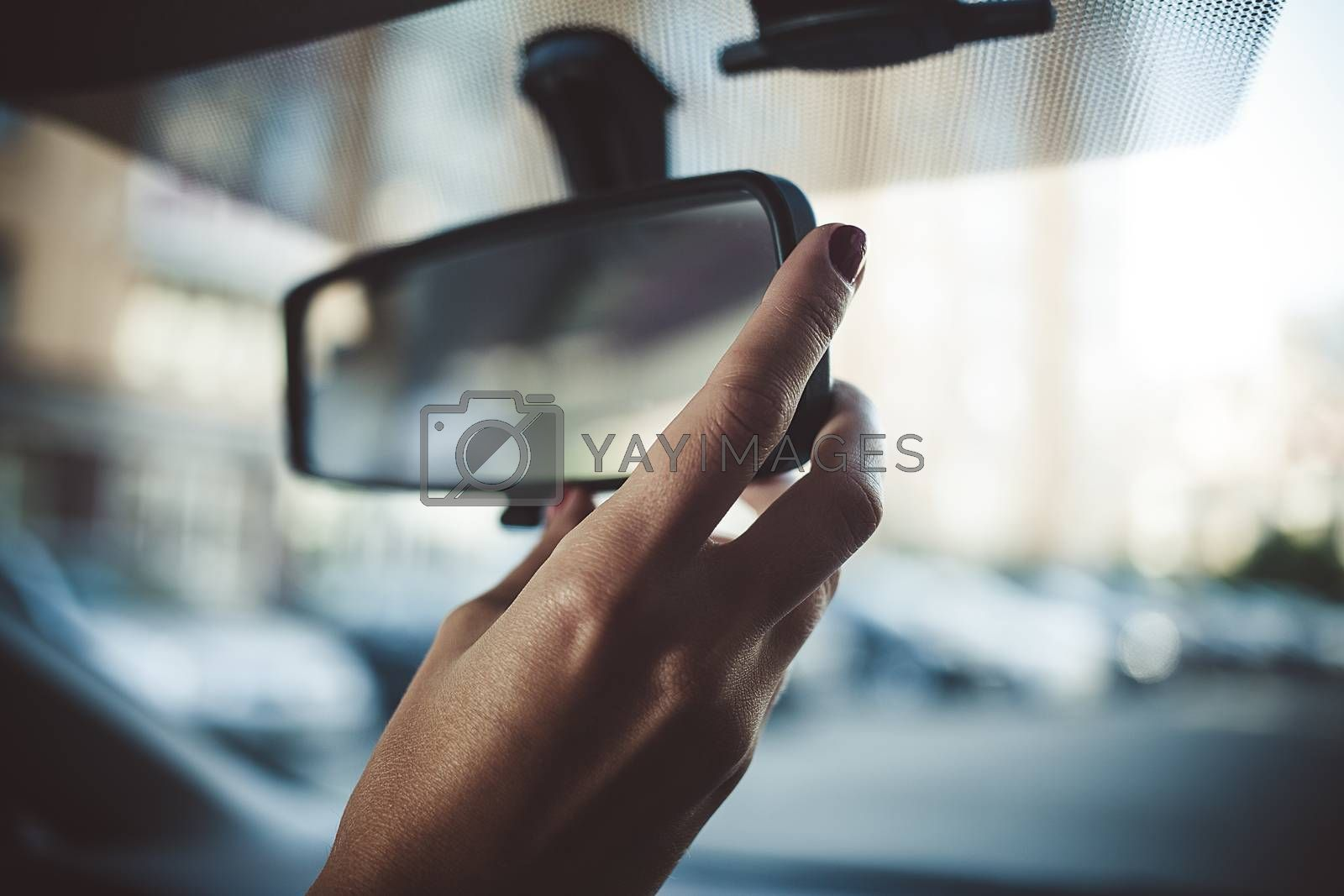 A man is driving a rear-view mirror in the car