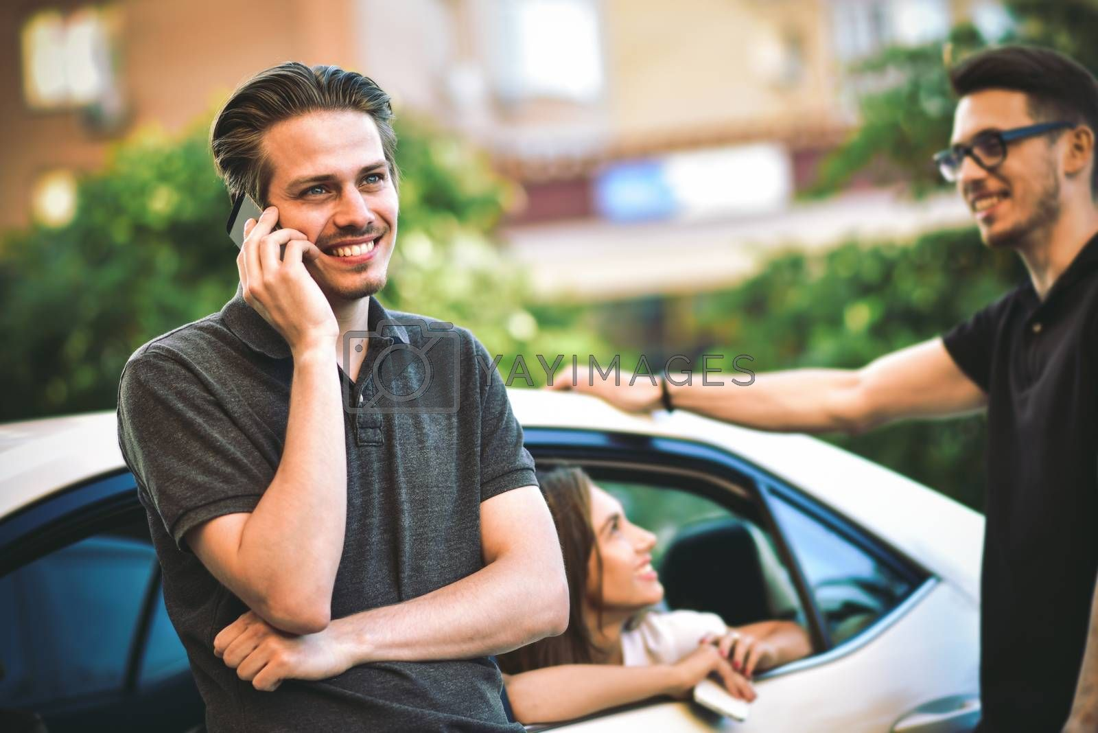 Handsome young caucasian man talking on the mobile phone and smiling while standing near the car with his friends chatting in the background.