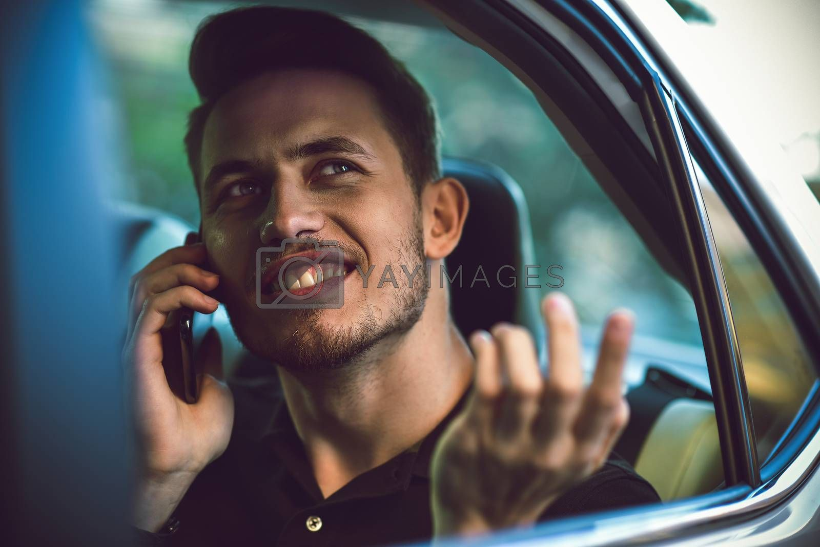 Passenger businessman use a smartphone in the back seat of the car. by Nickstock