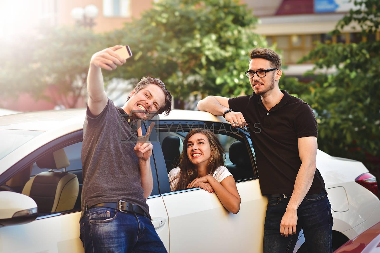 Three friends having fun taking a conversation near the car