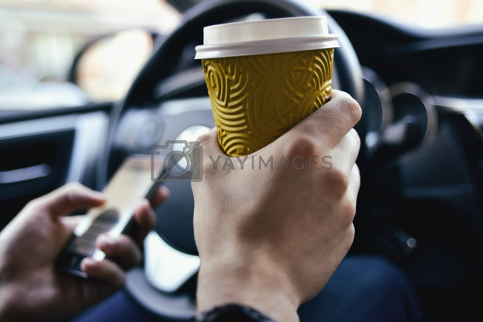Man arms hold a coffee and rudder in automobile