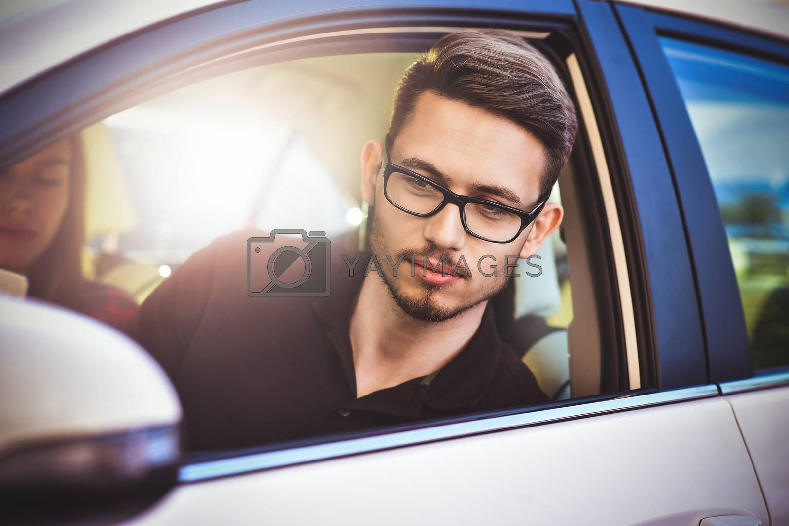 Enjoying travel. Beautiful young couple sitting on the front passenger seats and smiling while handsome man driving a car and use a mobile phone