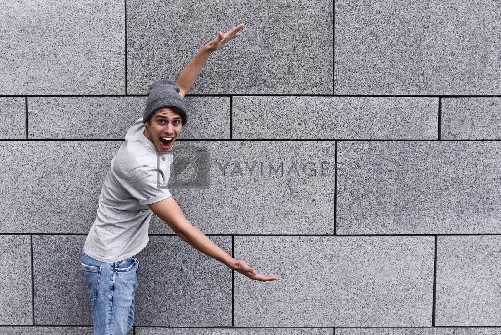 Cheerful guy dressed in gray t-shirt, sunglasses and hat at the street, show a big sale, or nice offer. Advertise concept. People, travel and tourism - man on city street show with his hands something over gray wall background