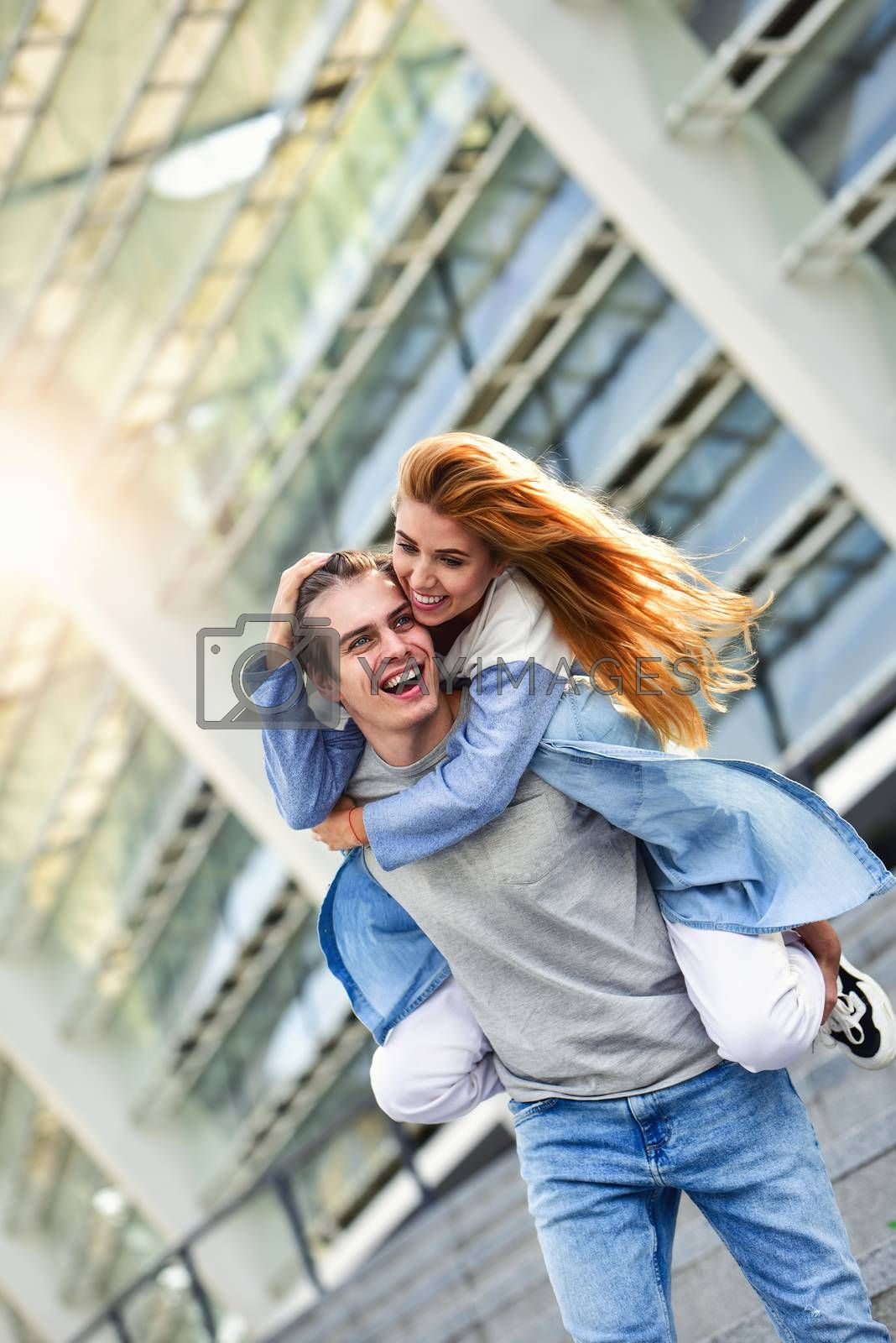 Man giving his pretty girlfriend a piggy back at street smiling at each other on a sunny day.