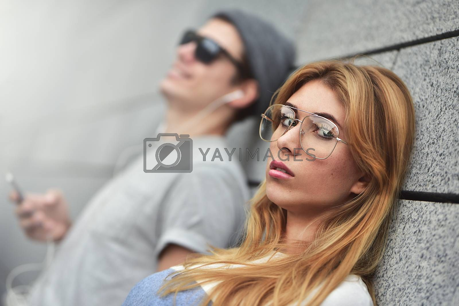 Portrait of Young attractive couple listening to music on the same pair of headphones, dressed in stylish clothes against a background of a gray wall.