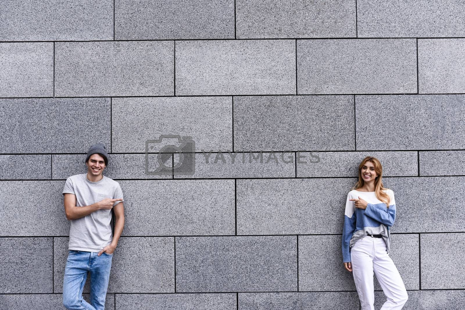 Cheerful couple at the street, show a big sale, or nice offer. Advertise concept. People, travel and tourism - on city street and couple show with their fingers something over gray wall background.