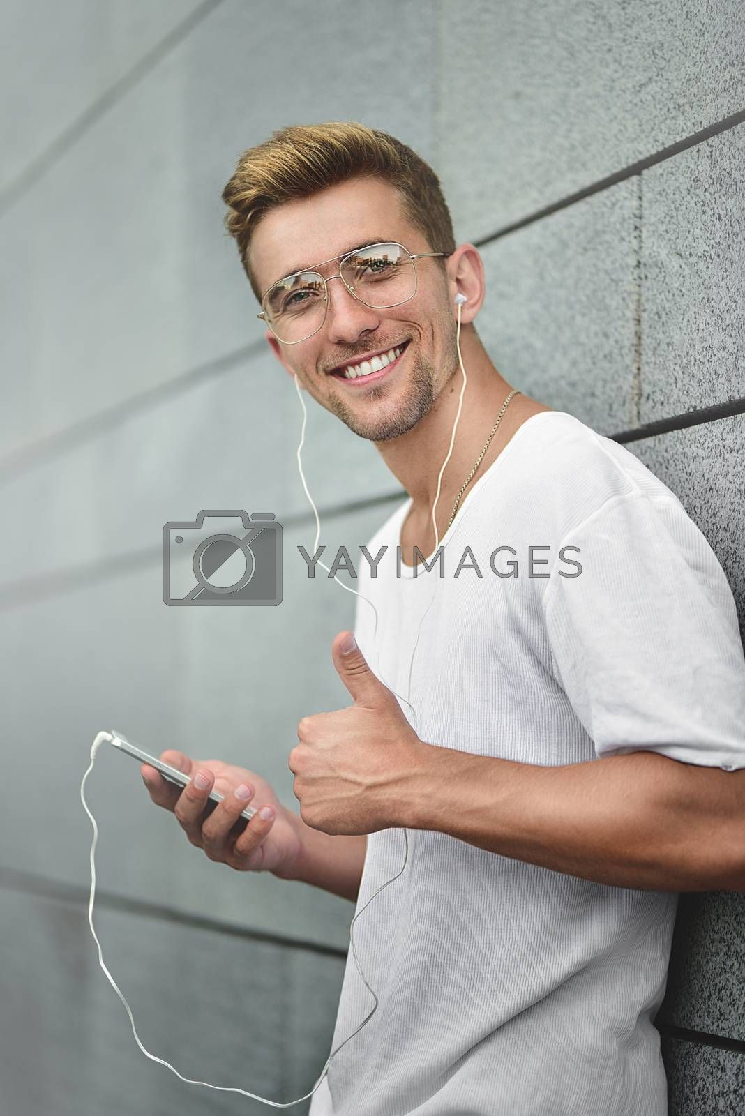 Cheerful guy dressed in white t-shirt at the street, listening to music with earphones, holding mobile phone. by Nickstock