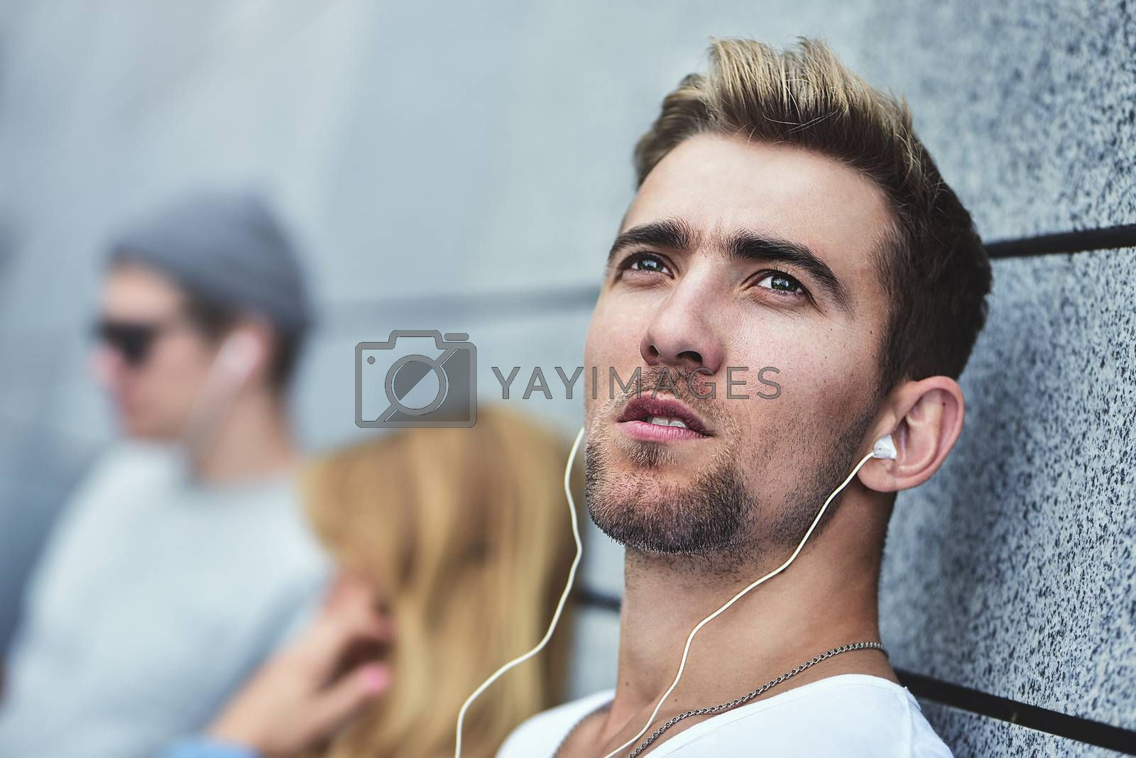 Portrait of Young attractive Teens listening to music on the same pair of headphones, dressed in stylish clothes against a background of a gray wall.