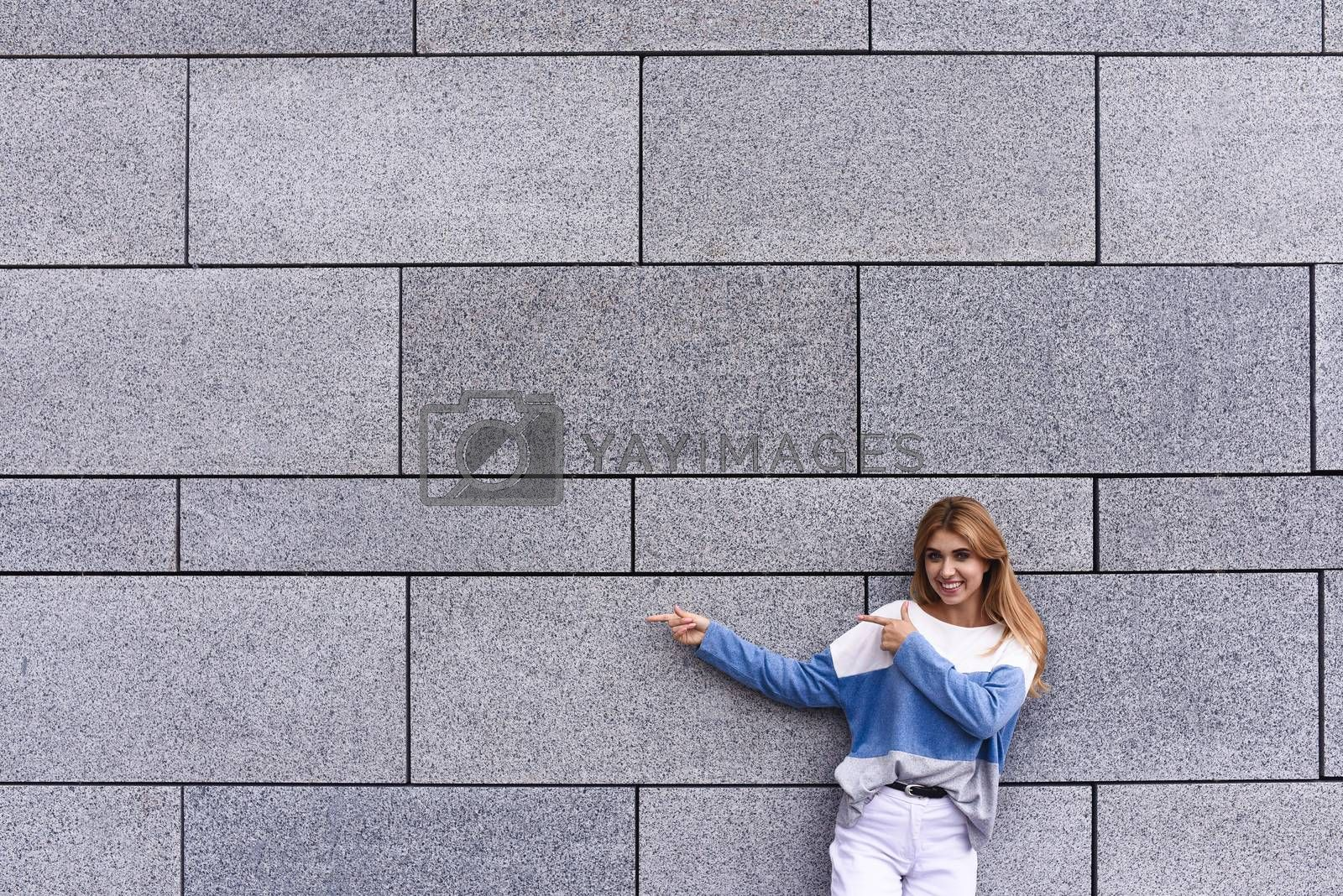 Cheerful girl at the street, show a big sale, or nice offer. Advertise concept. People, travel and tourism - woman on city street and girl show with her finger something over gray wall background