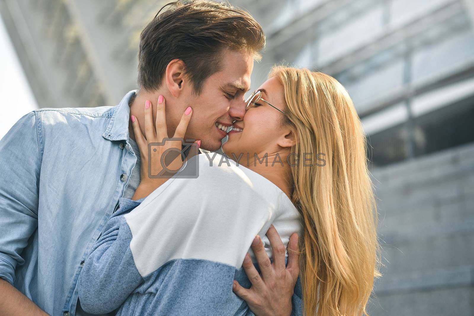 Young beautiful couple outdoor fashion portrait. Attractive boy and girl hugging and kissing.