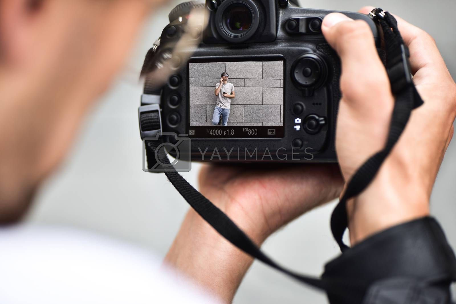 Digital single-lens reflex camera in hands. Photographer shooting hands close up. Man photographer makes photos for stock photography. Male hands hold the camera close-up