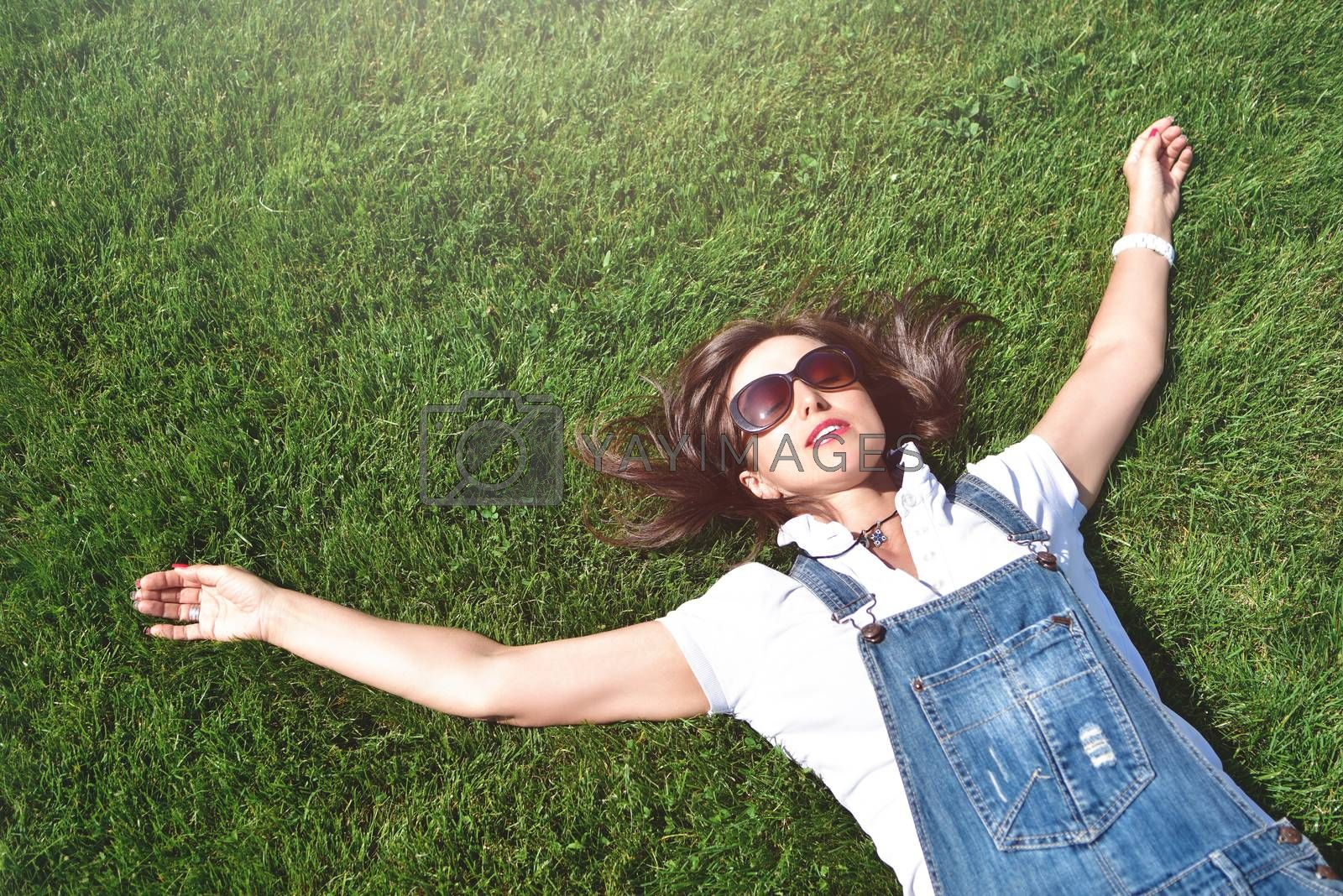 summer-vacation, girl relaxed lying on green grass in an outdoor park. girl in sunglasses enjoying nature lying on grass