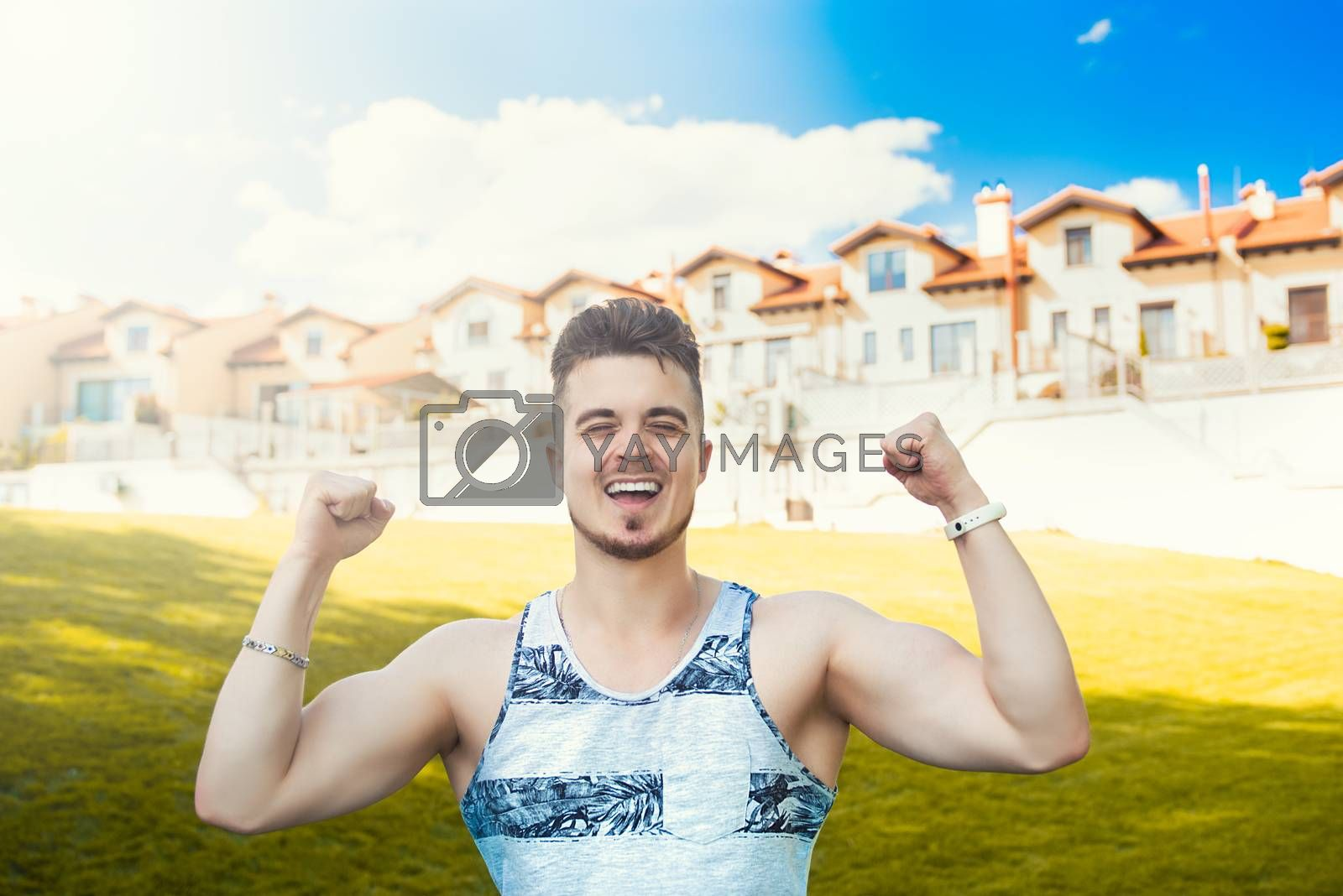 Expressive emotion. Attractive vacation. Happy young man got good news. beautiful cottages in the background.