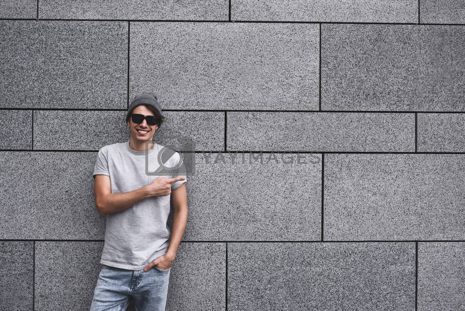 People, travel and tourism - man with Sunglasses on city street and guy show with his finger something over gray wall background