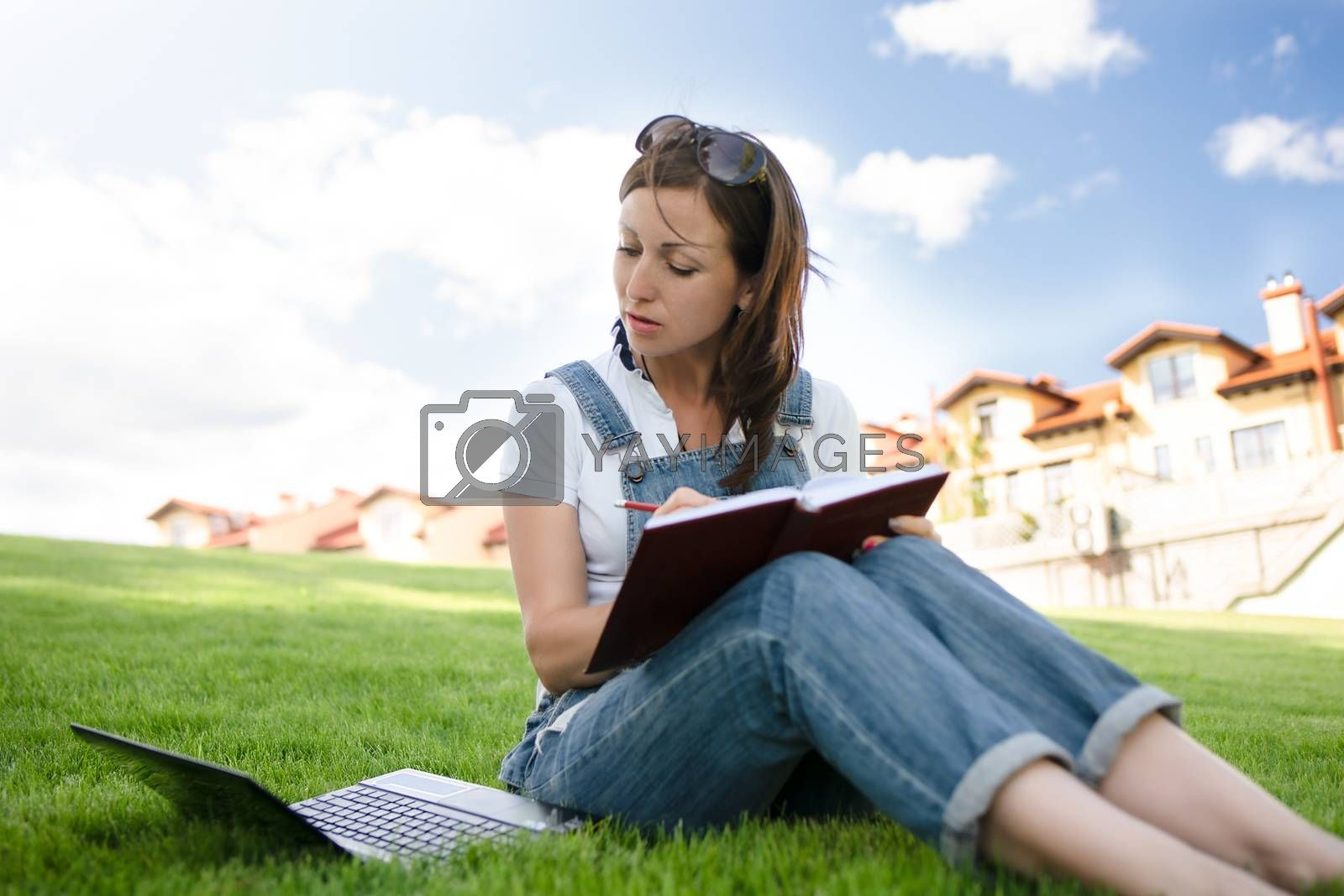 pretty woman sitting on green grass in park with laptop on legs, spending summer day working outdoor, using laptop and wireless Internet for online work. Lifestyle concept.