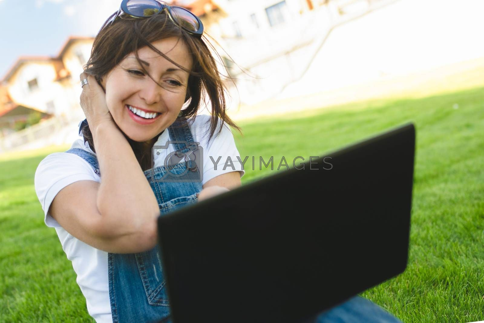 Female gets joyful emotions by talking to her friends on a conference call from notebook ,she dressed in jeans overalls sitting on grass in the park