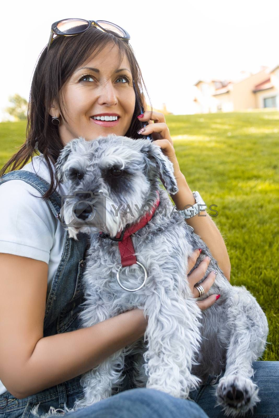 Portrait of a happy caucasian woman who hugs her beloved dog and talking by the phone.The concept of love for animals. best friends.