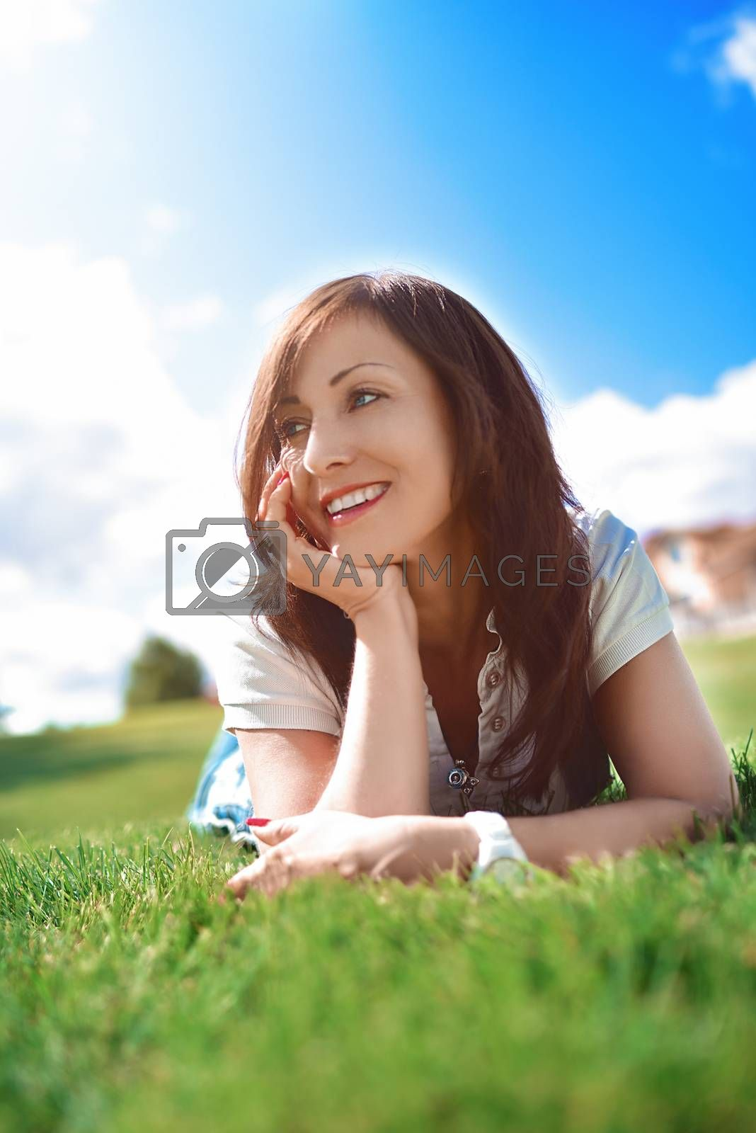 Positive emotion, adult woman relaxed lying on green grass in an outdoor park. girl in sunglasses enjoying nature lying on grass by Nickstock