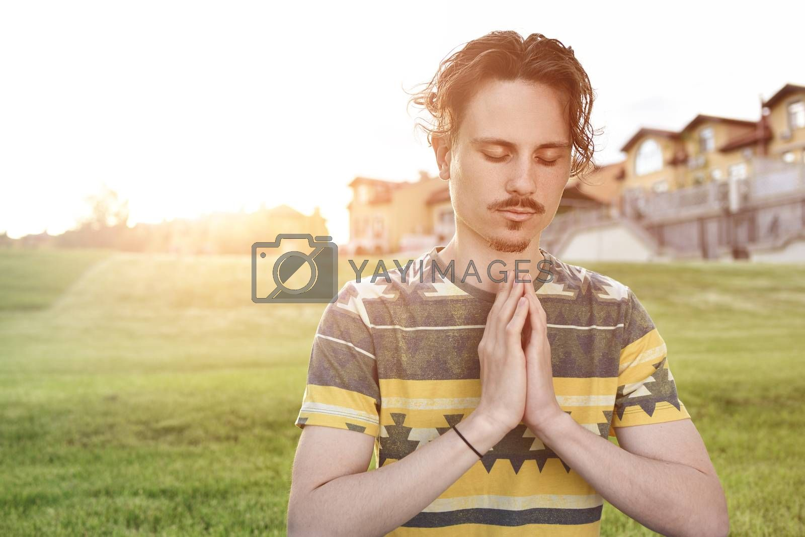 Young man meditating outdoors in the park, sitting with eyes closed and his hands together. man praying to god