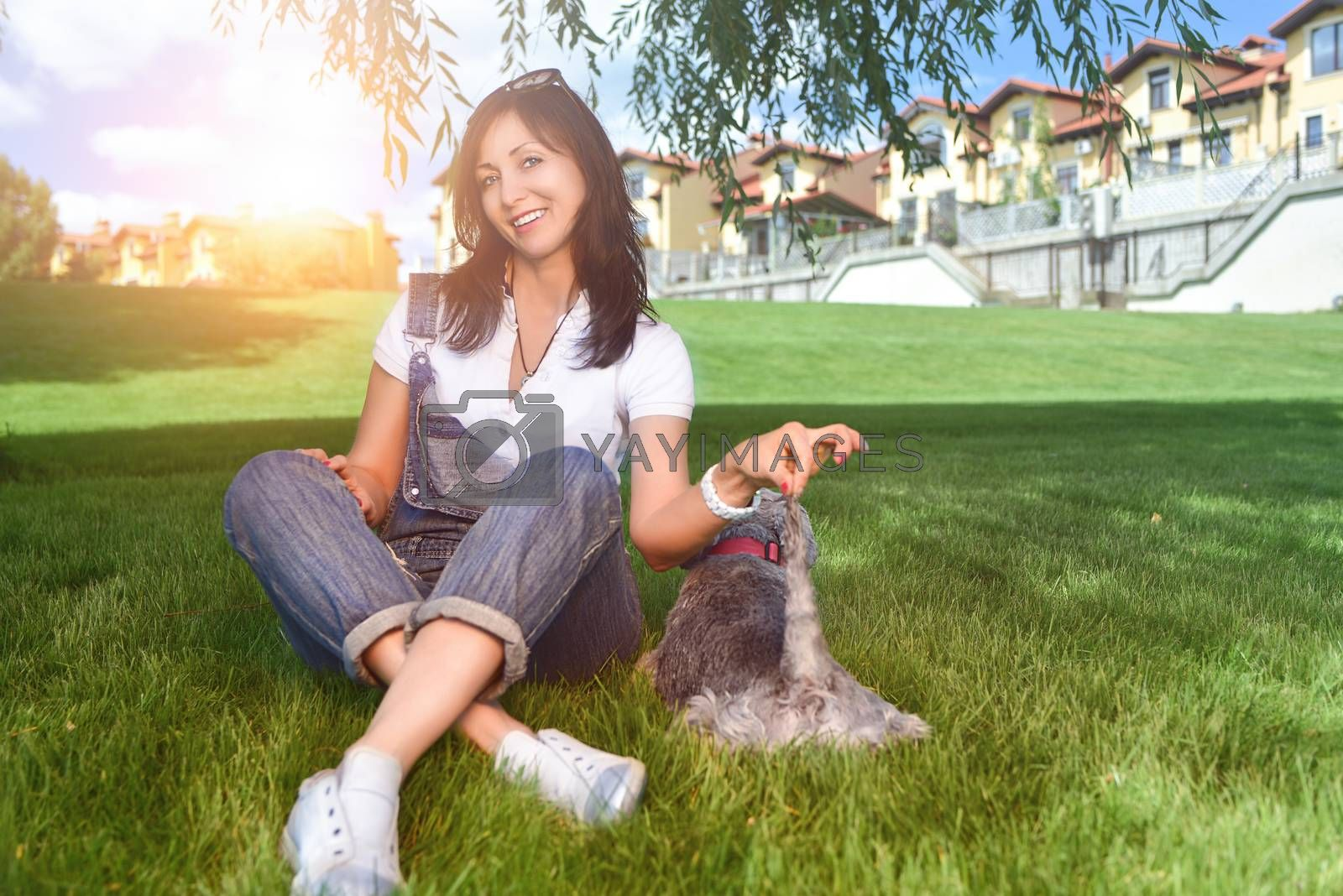 Caucasian joyful woman playing with her beloved dog in the park. The concept of love for animals. best friends. Dog breed Schnauzer