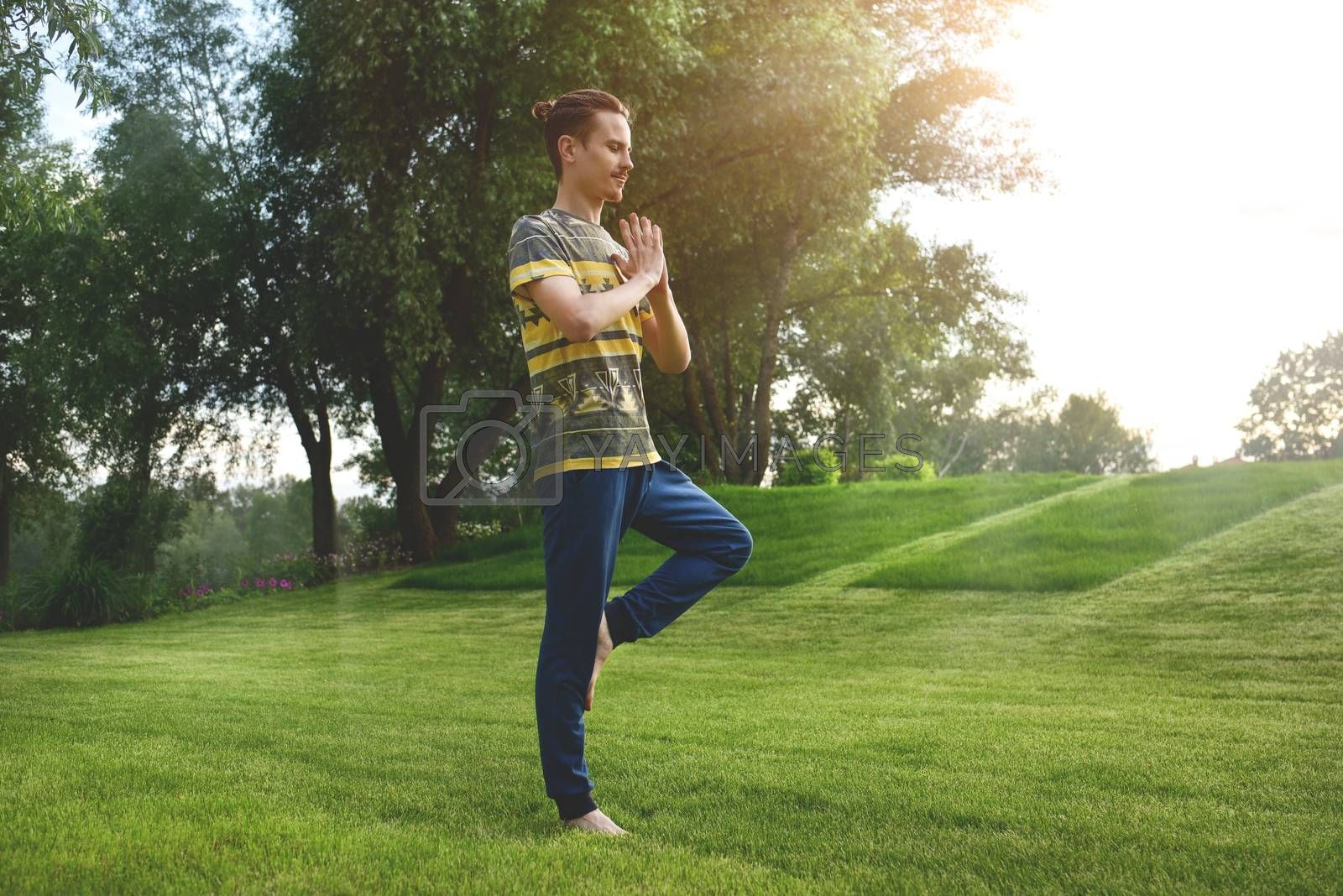 Fitness man doing exercise on one leg isolated in the park. enjoying nature, yoga and meditation concept. spiritual practices.