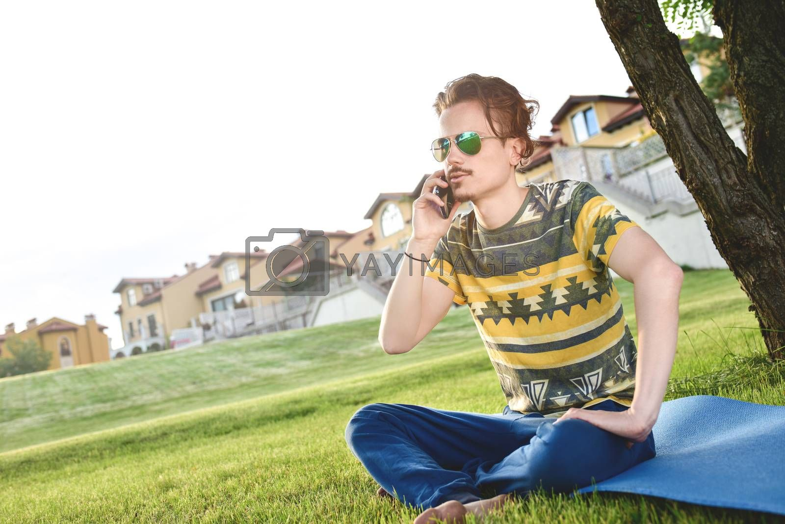 young stylish handsome guy is sitting on grass and talking on the phone resting in the park. Taking a Break
