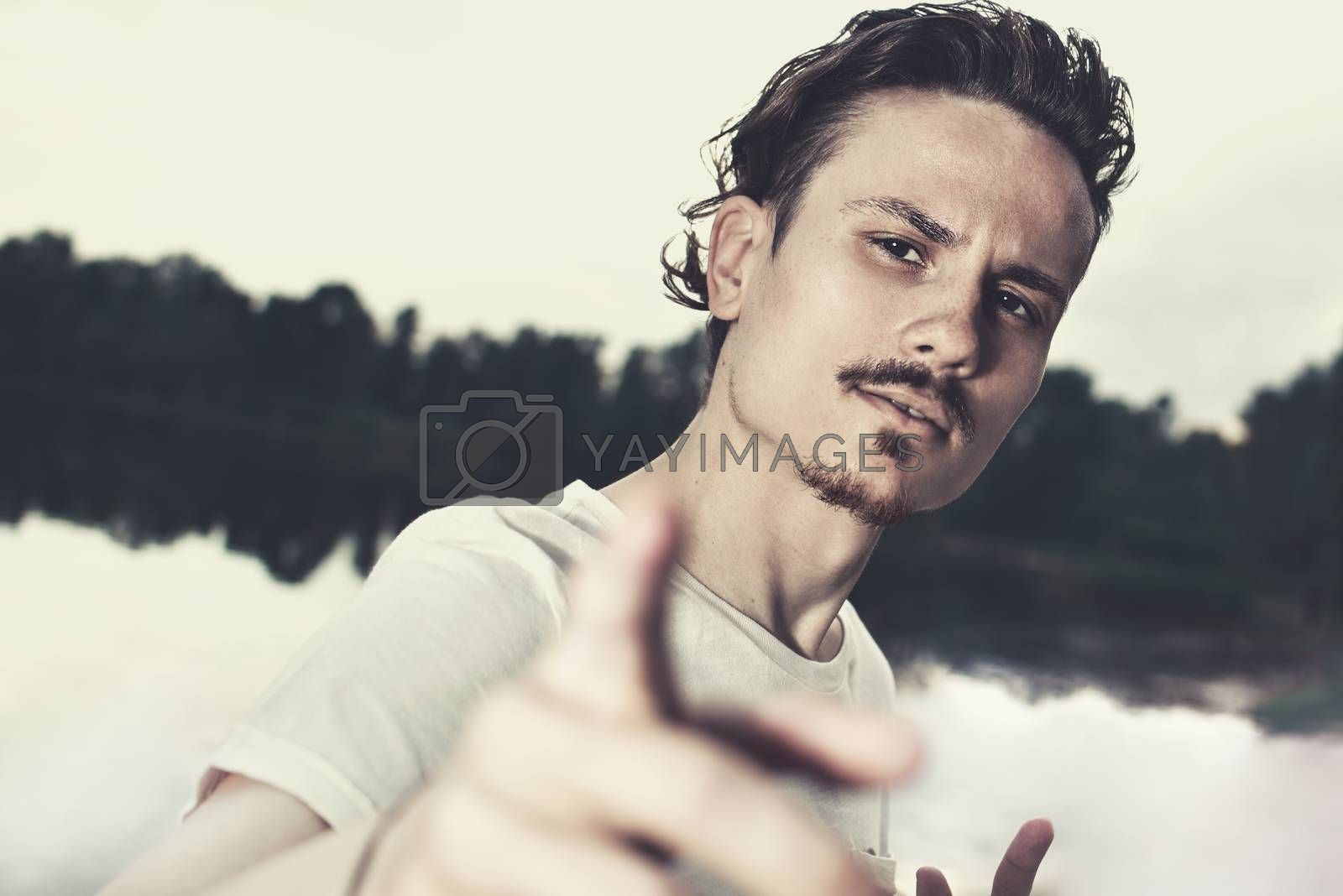 portrait of a brutal stylish guy aggressively looking into the camera. black and white photo. selfie photo. the guy challenges the opponent. provokes conflict