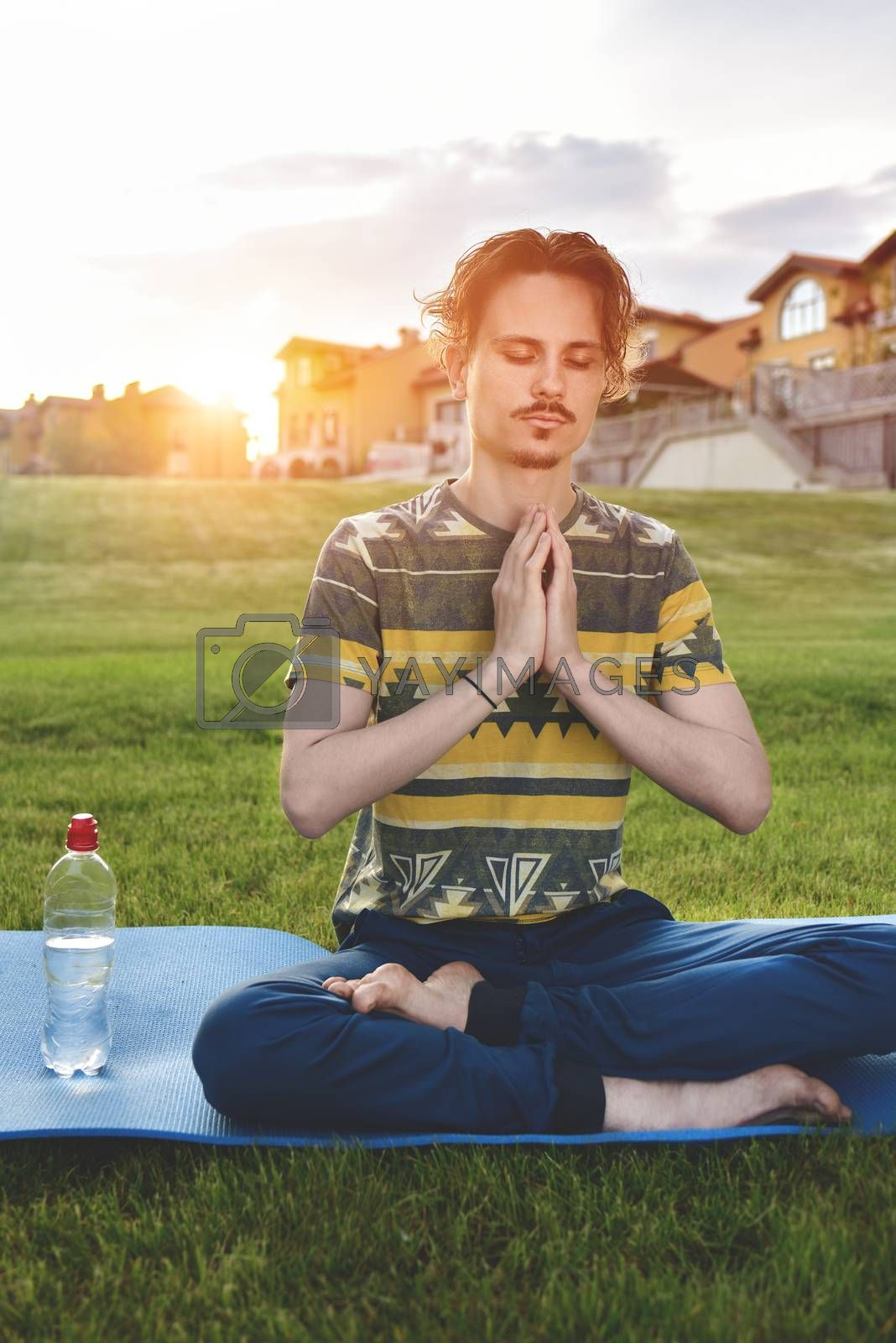 Young man meditating outdoors in the park, sitting with eyes closed and his hands together.enjoying nature, yoga and meditation concept. spiritual practices.zen by Nickstock