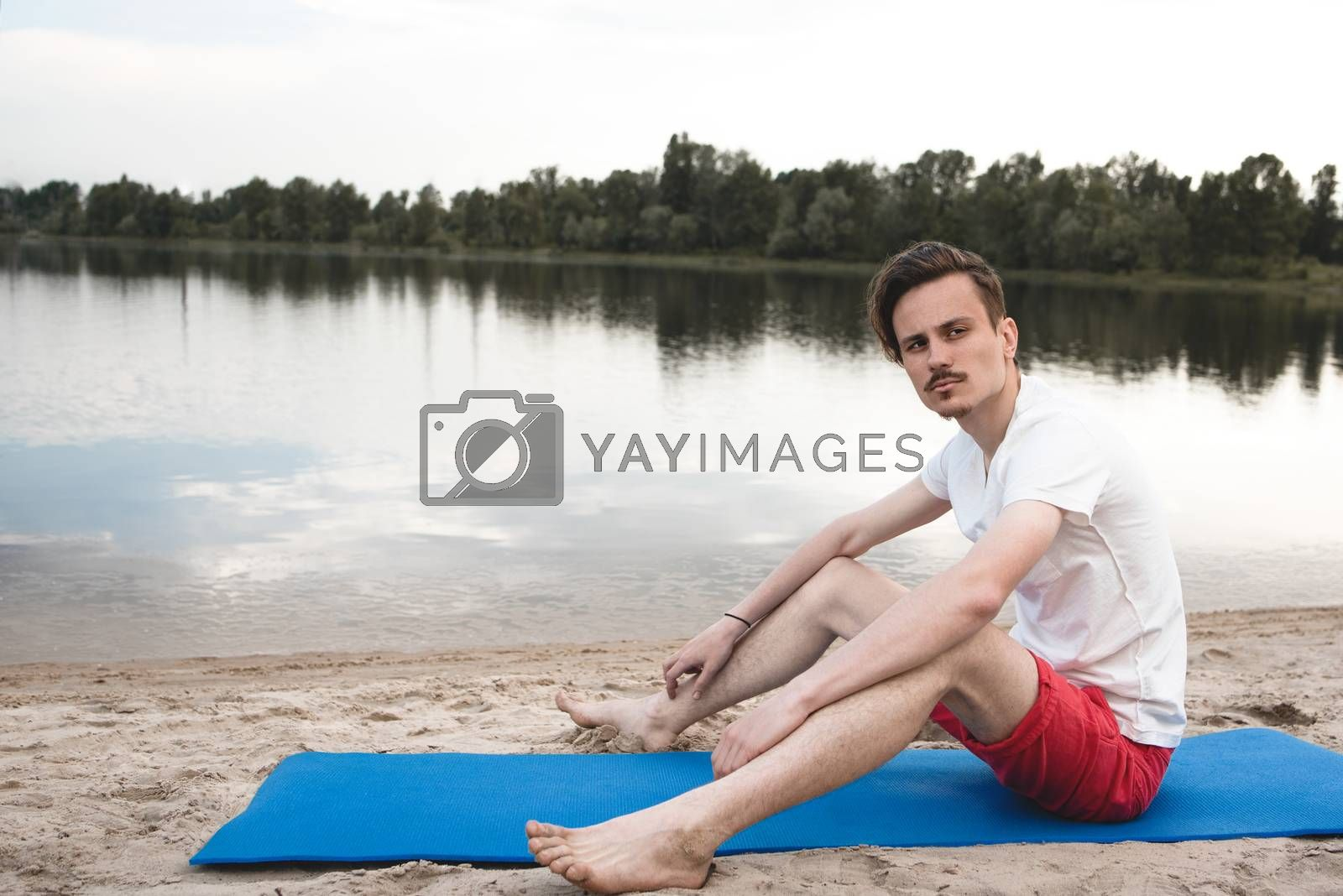 Young man relax siting on beach looks to right with sky. Conceptual for thinking and looking for concentrate somethings in Summer background
