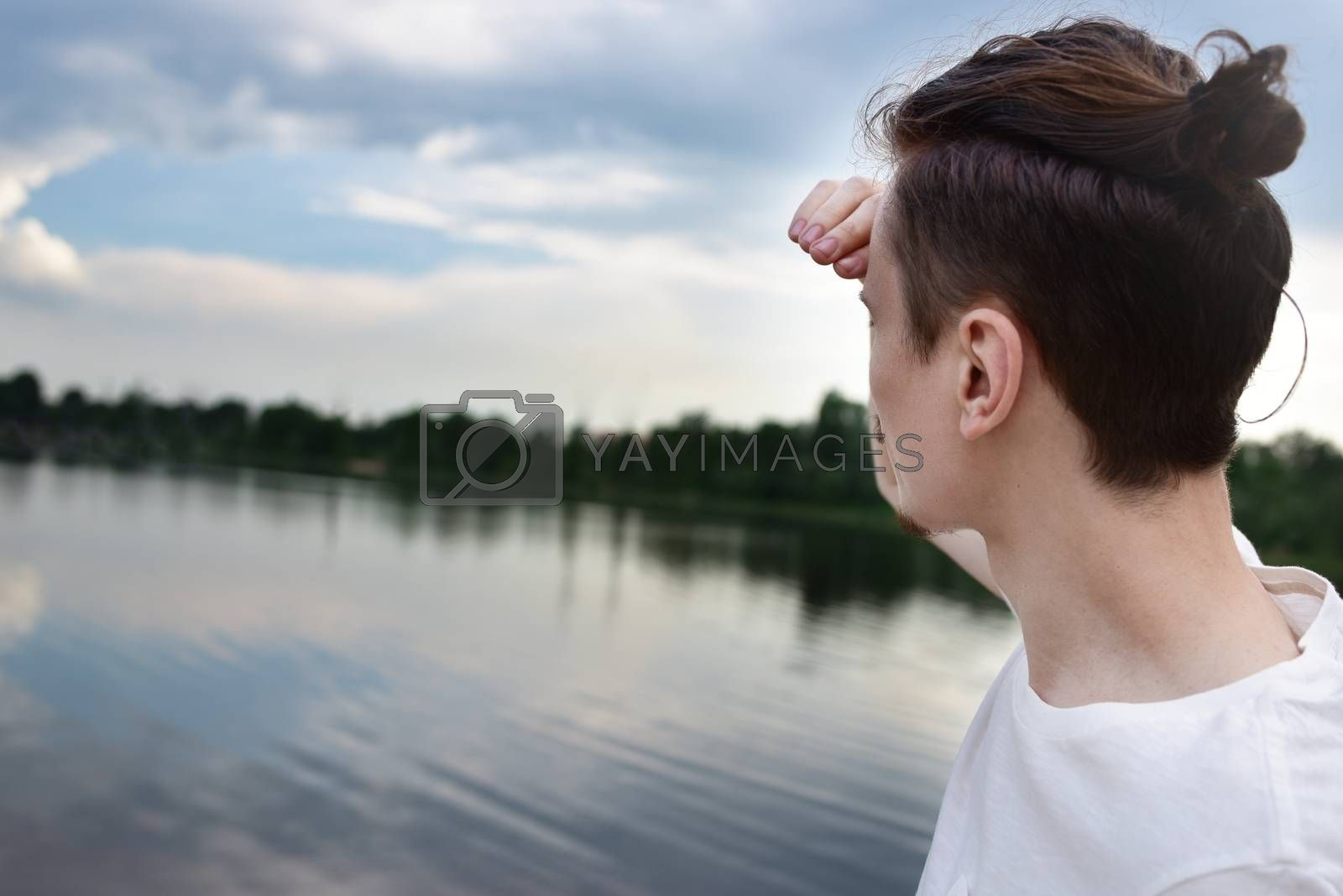 Man looks into the distance near a lake and forest. Enjoys a beautiful view. summer . spring nature