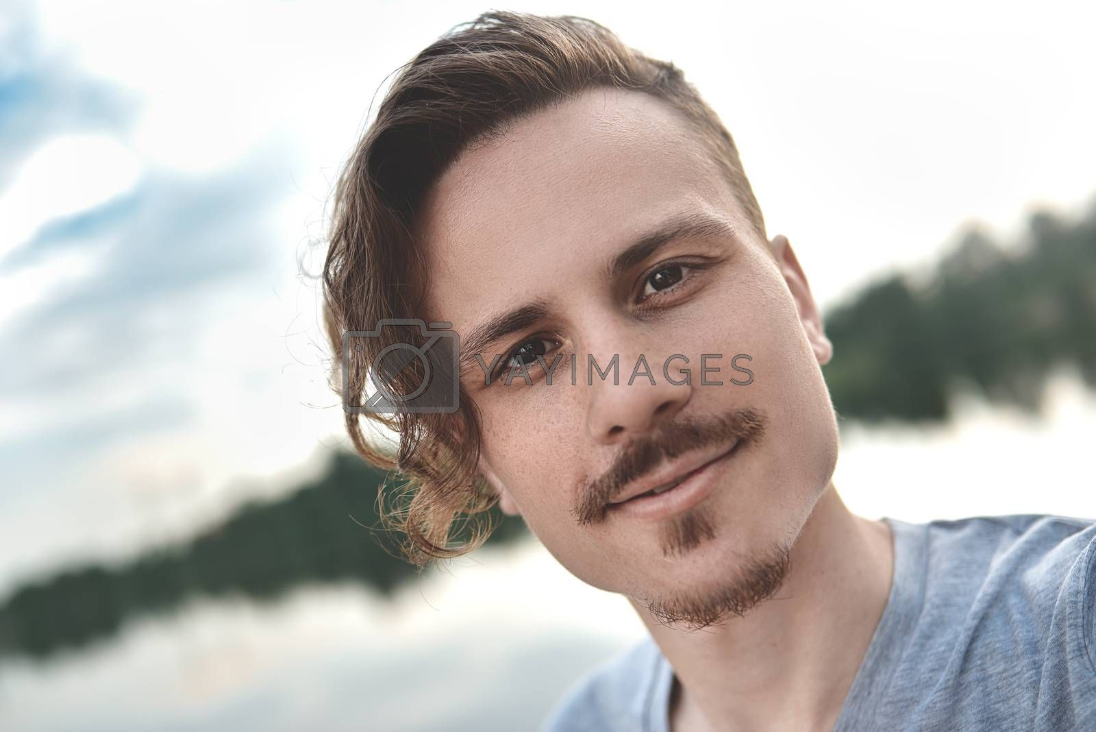 Handsome caucasian guy takes a selfie at the beach - people, lifestyle and technology concept