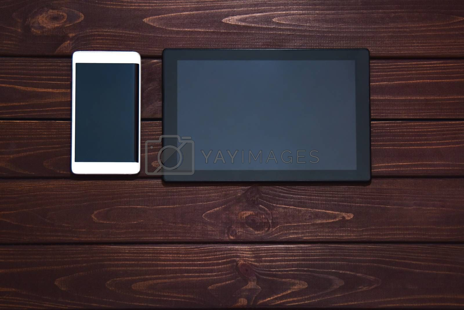 modern smart phone and tablet pc on wooden table. technology concept. free copyspace