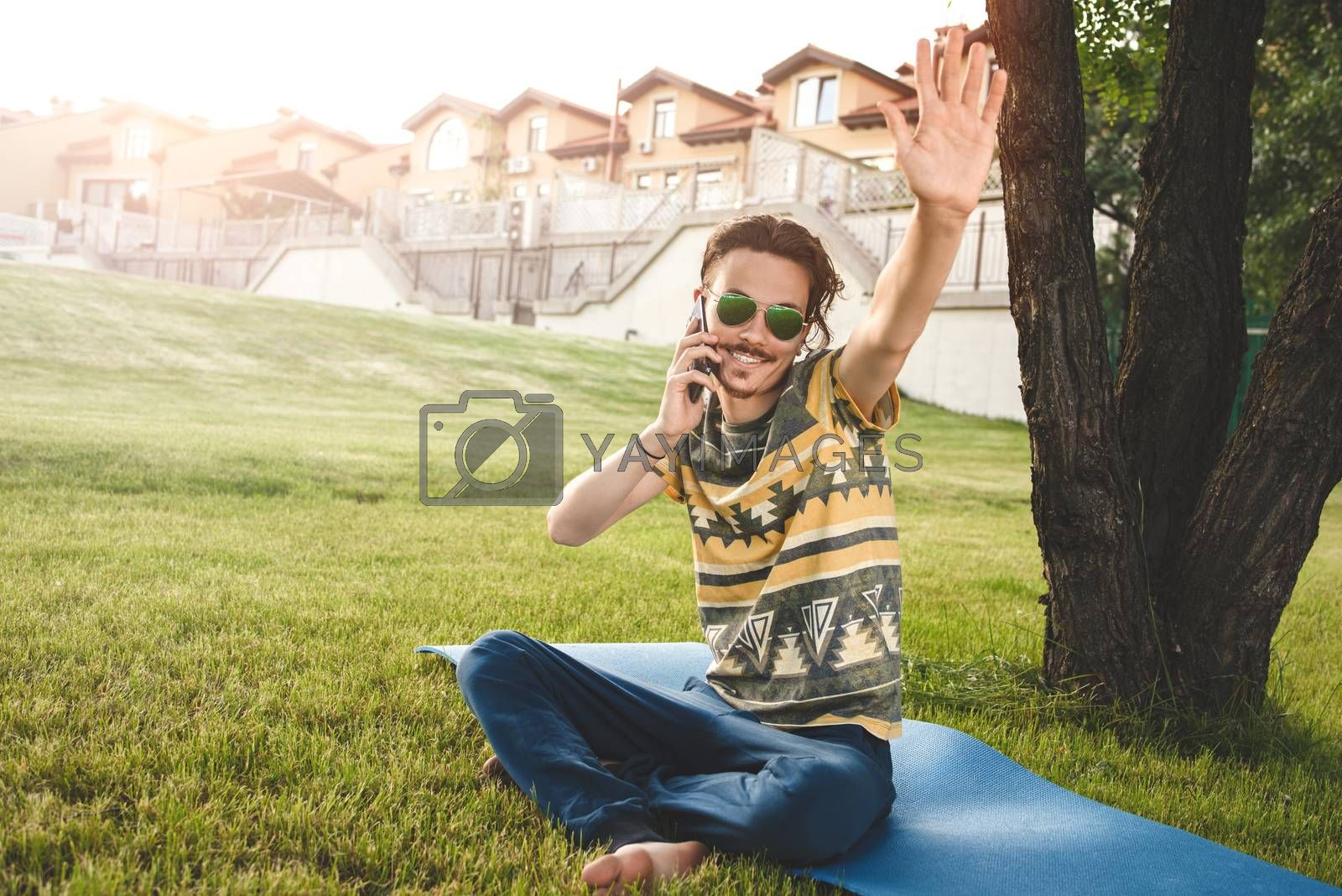 young stylish handsome man is sitting on grass, resting and talking on the phone. waves his hand welcoming friends