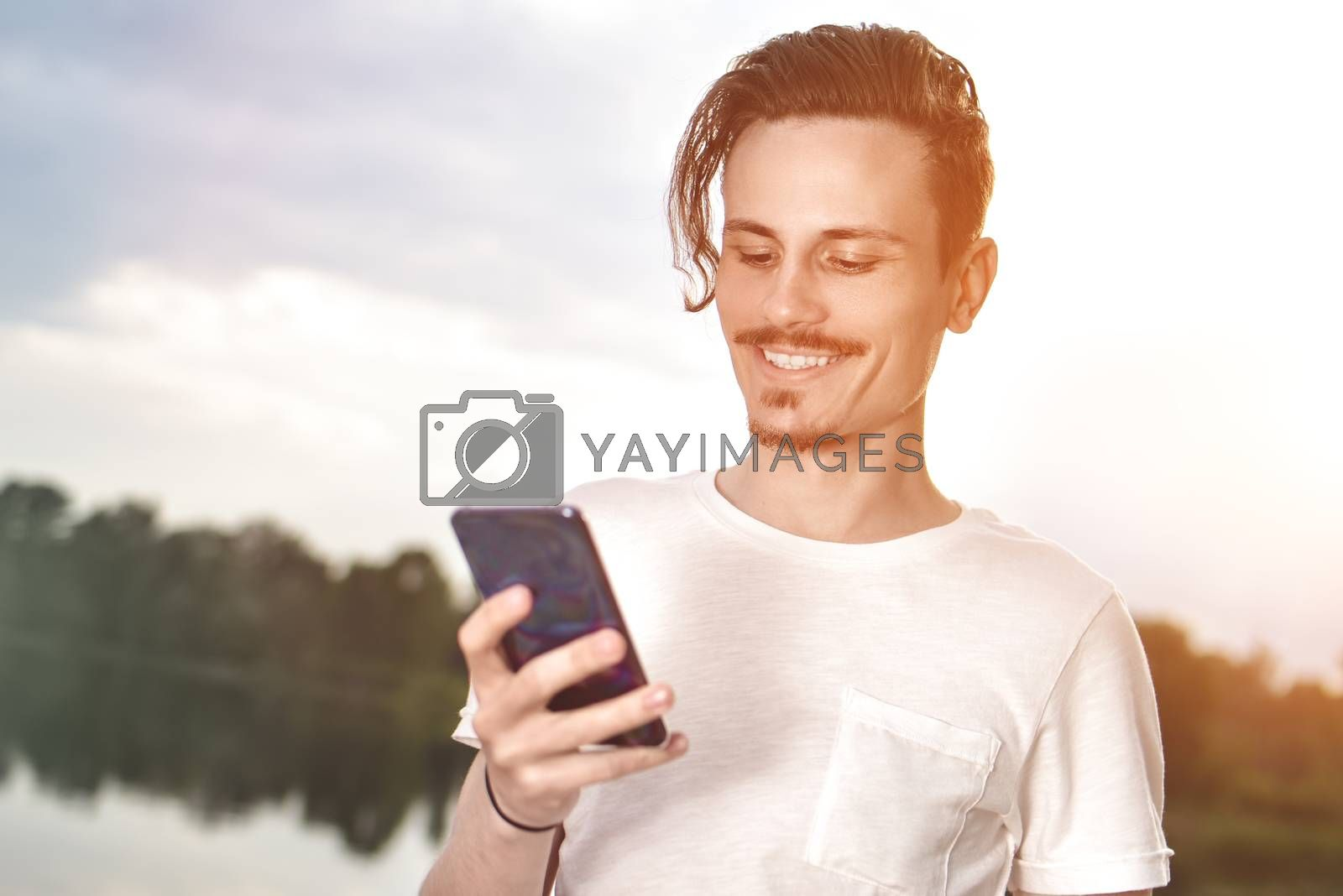 Young man walking near beautiful bay using phone and headphones for communicate with friends . good mood, beautiful view